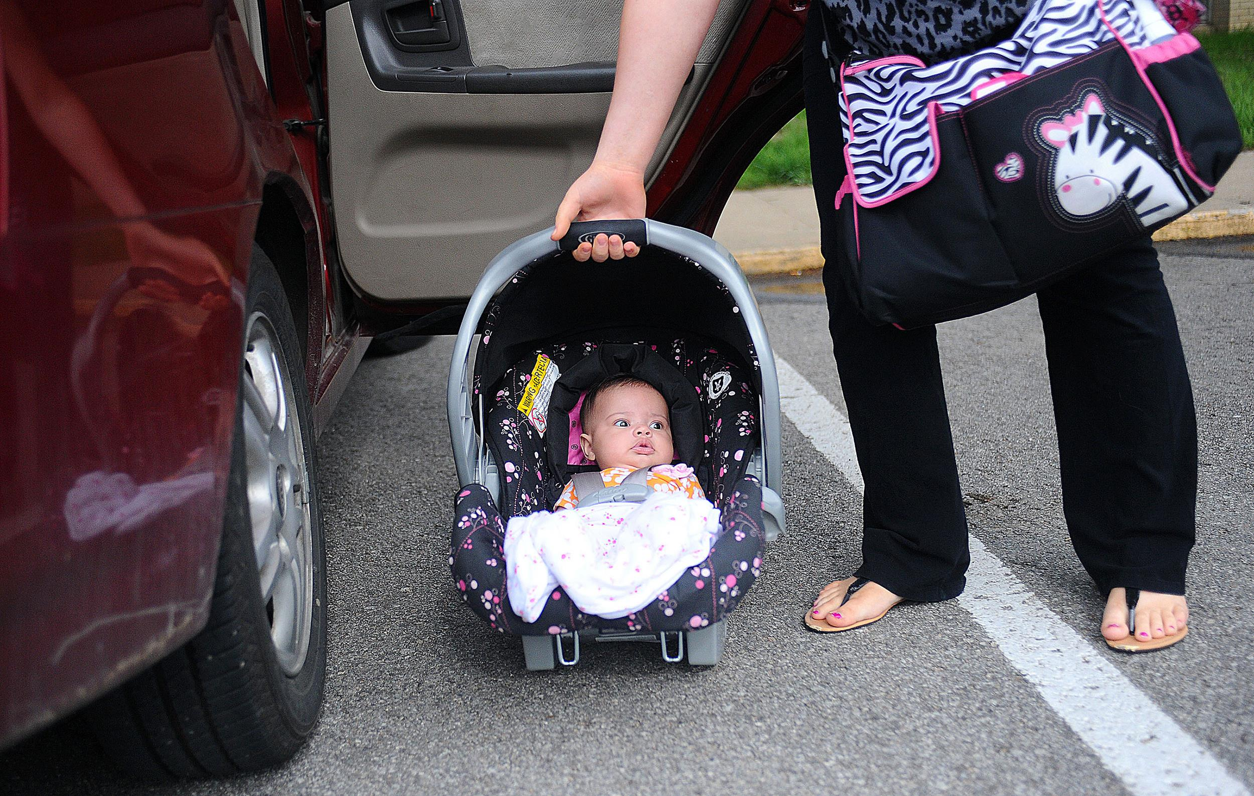 Image: A baby waits to be loaded into the car by her mother outside of St. Paul Lutheran in St. Joseph, Mo. on May 9, 2013.