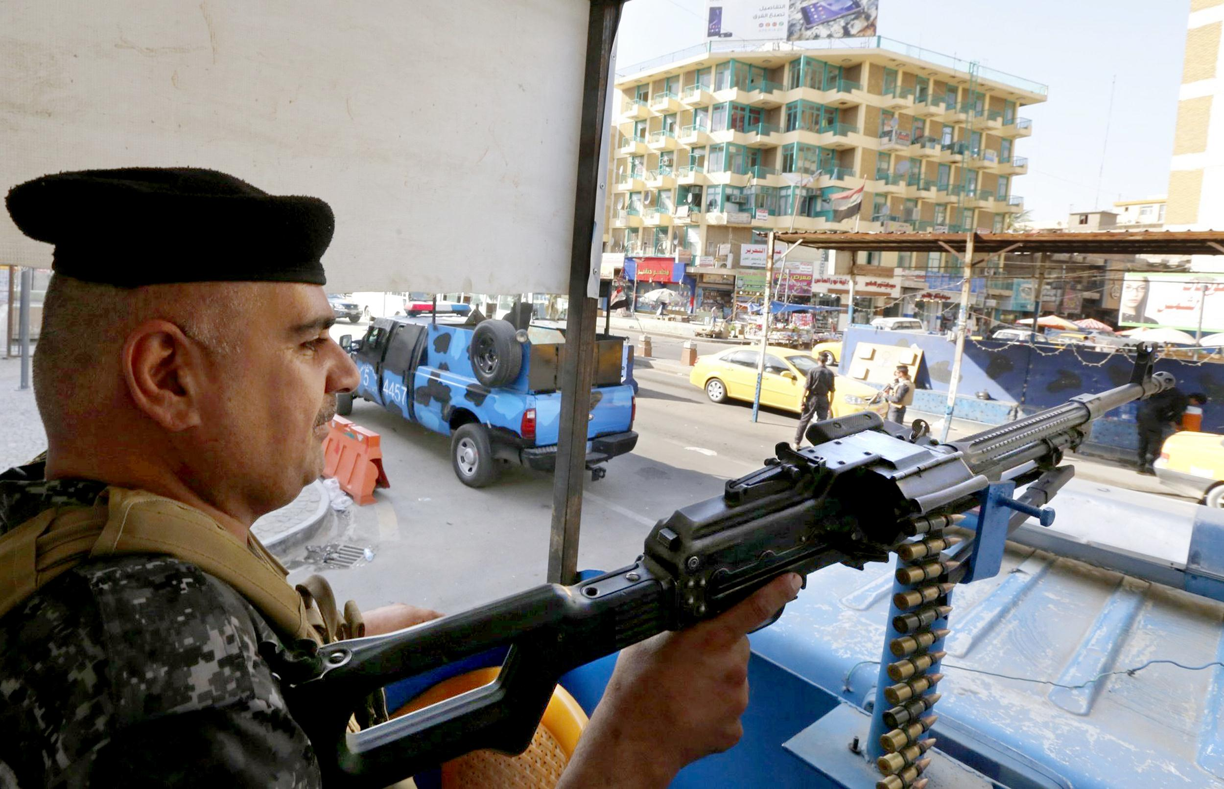 Image: A member of the Iraqi security forces guards a checkpoint during an intensive security deployment in Baghdad
