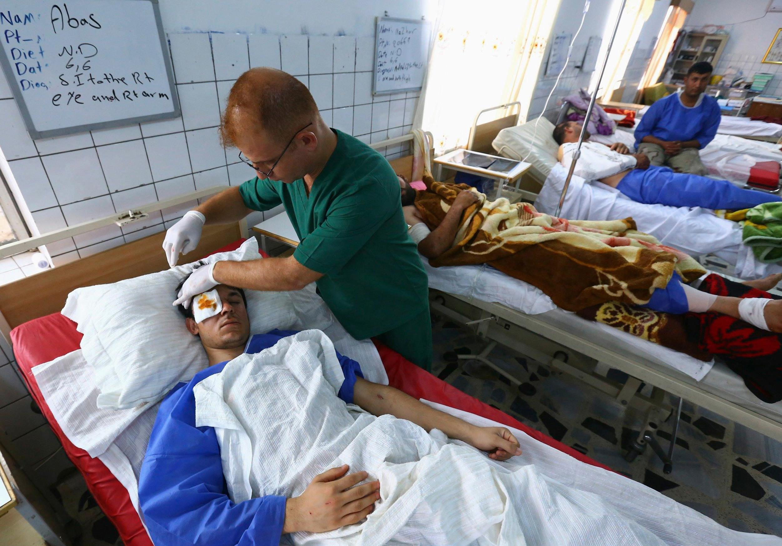 Image: A man, who was injured during a suicide bomber attack in Mwafaqiya village at Mosul, receives treatment in a hospital in Erbil