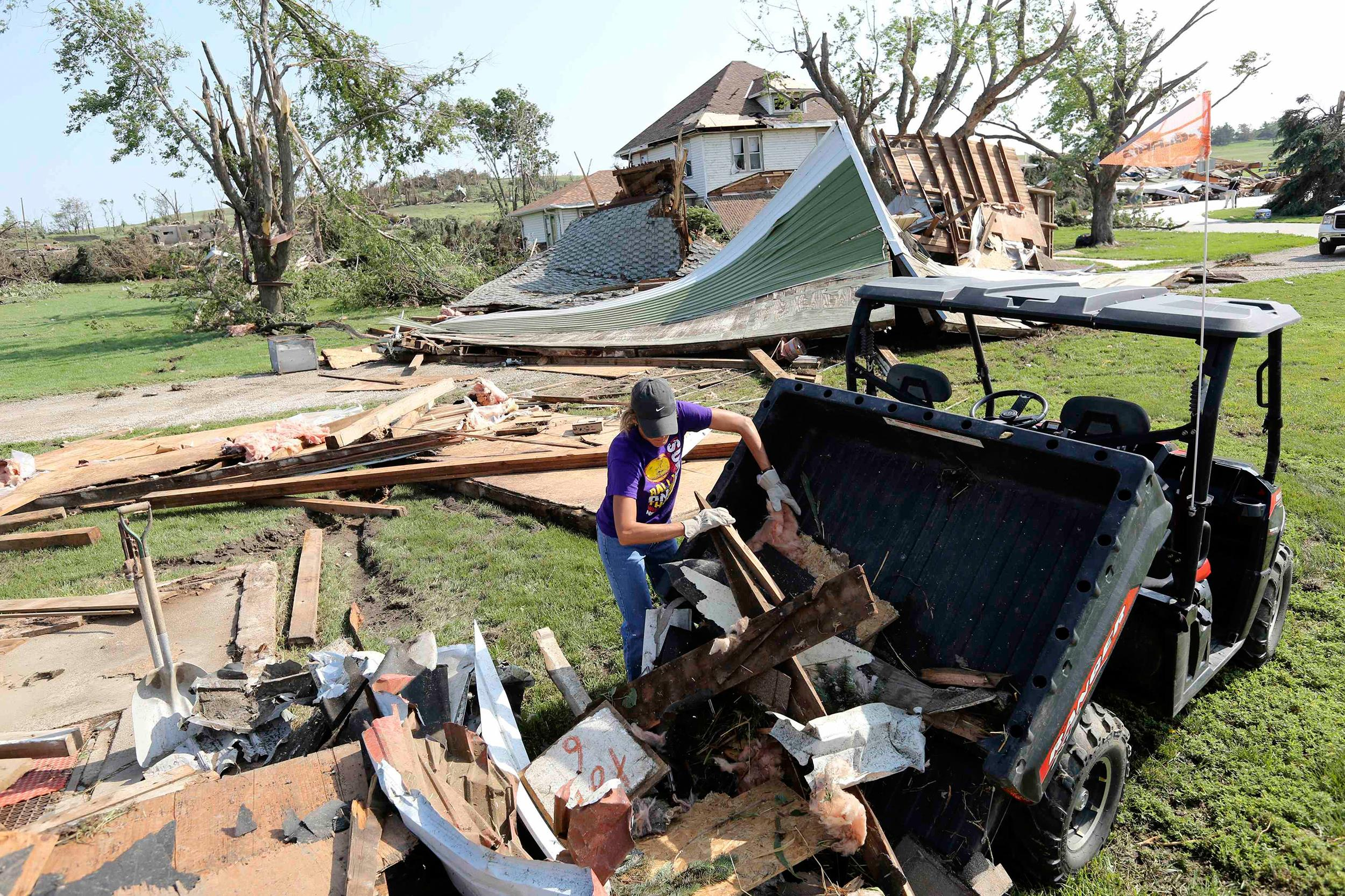Image: Tammie Batenhorst helps clean up storm debris outside of Pilger, Nebraska