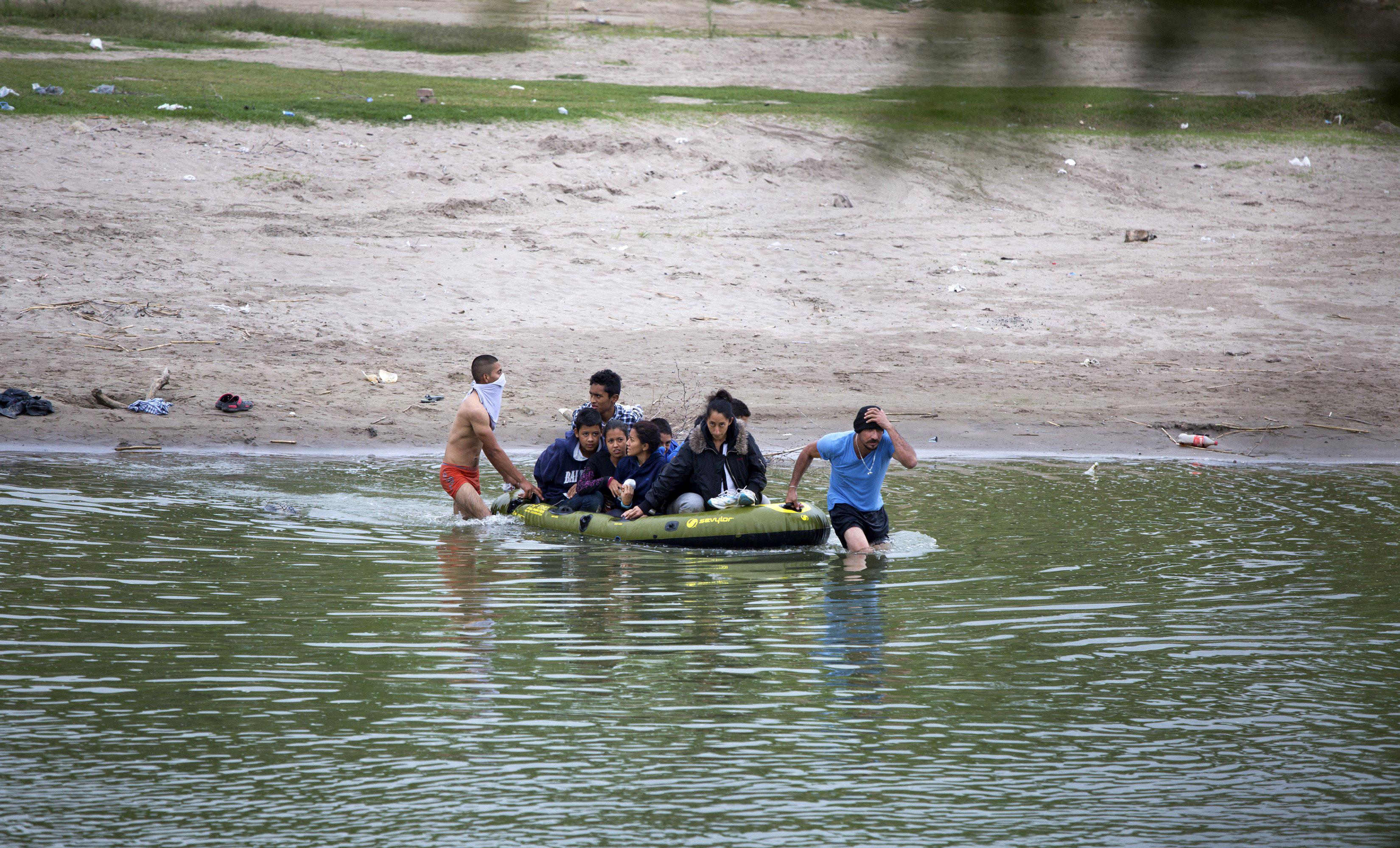 Image: Two guides lead a raft full of migrants across the Rio Grande