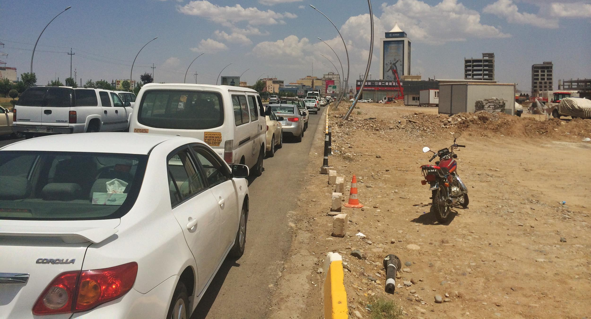 Image: At least 200 cars wait in line for gas at a petrol station in Erbil