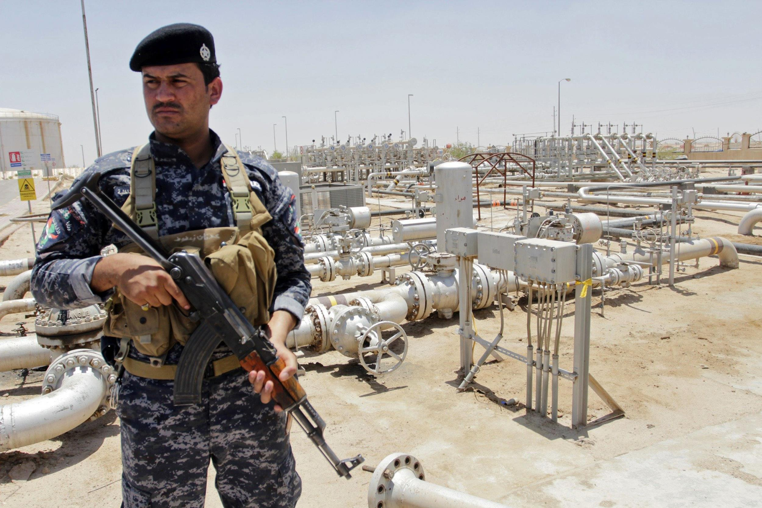Image: A member from oil police force stands guard at Zubair oilfield in Basra, southeast of Baghdad