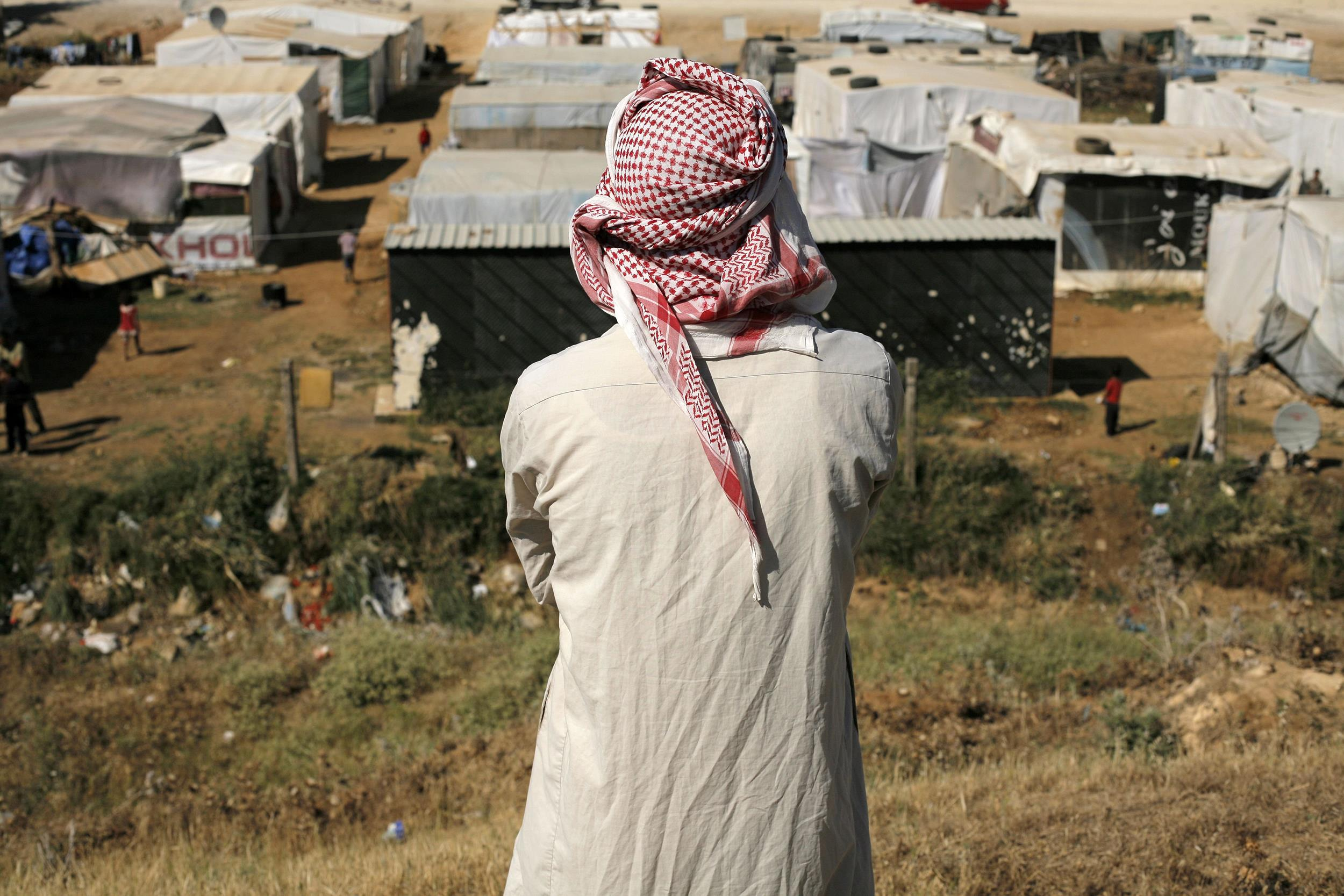 Image: A man looks at a Syrian refugee camp in the Lebanese village of Zahle in the Bekaa valley on June 17.