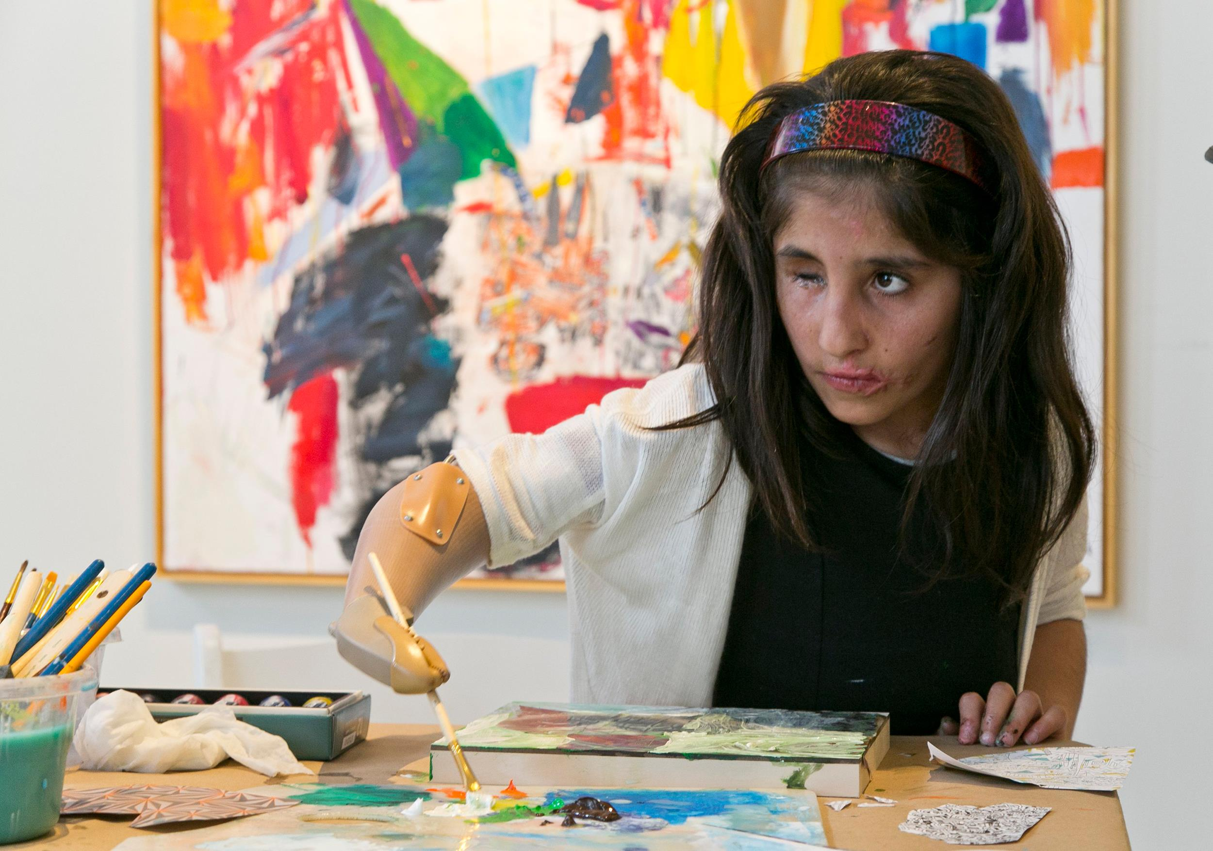 Image: Afghan war victim Shah Bibi Tarakhail uses her new prosthetic arm to paint during a private session with artist Dayvd Whaley in April
