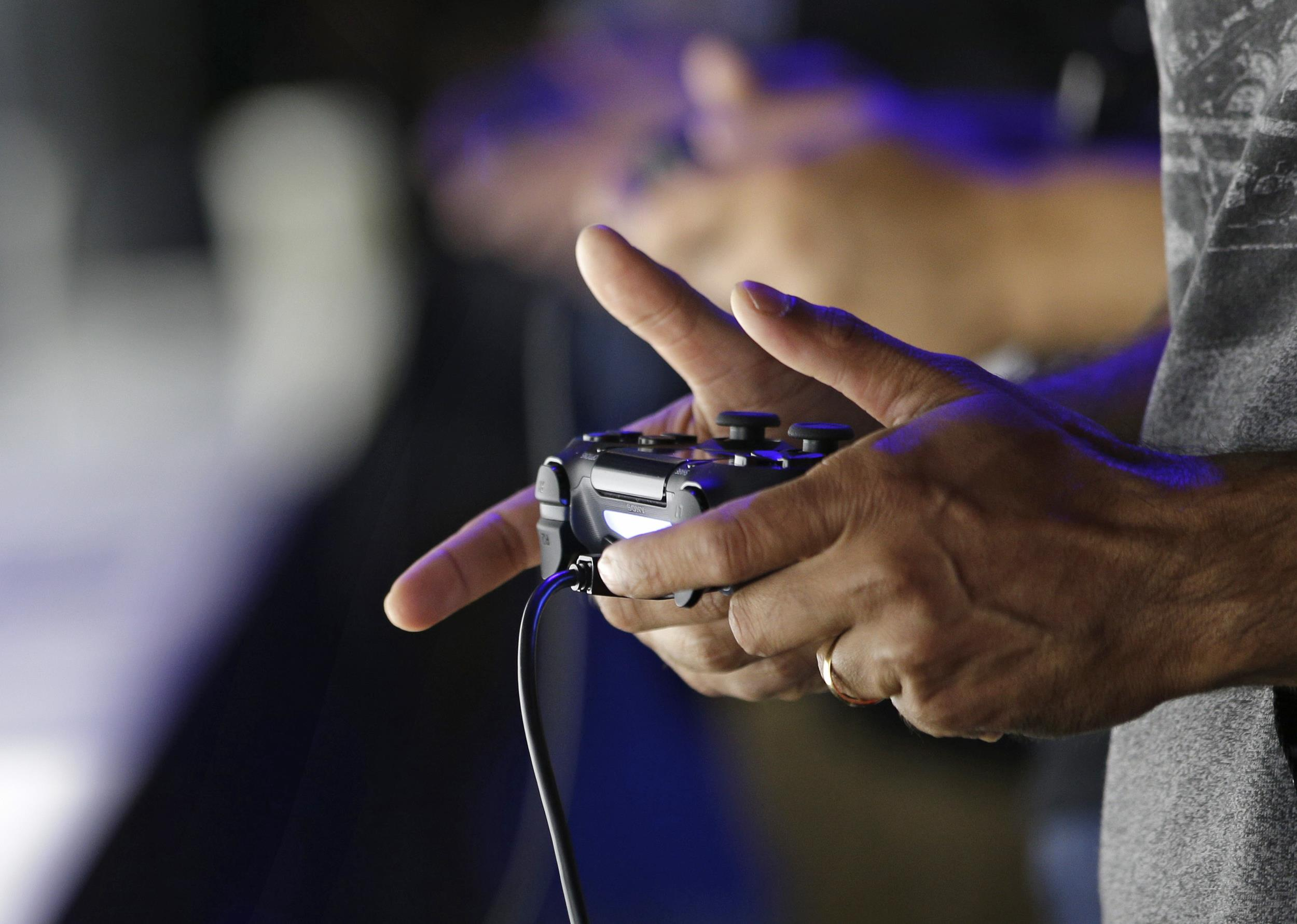 Attendees play video games on the PlayStation 4 at the Sony booth during the Electronic Entertainment Expo in Los Angeles in 2013.