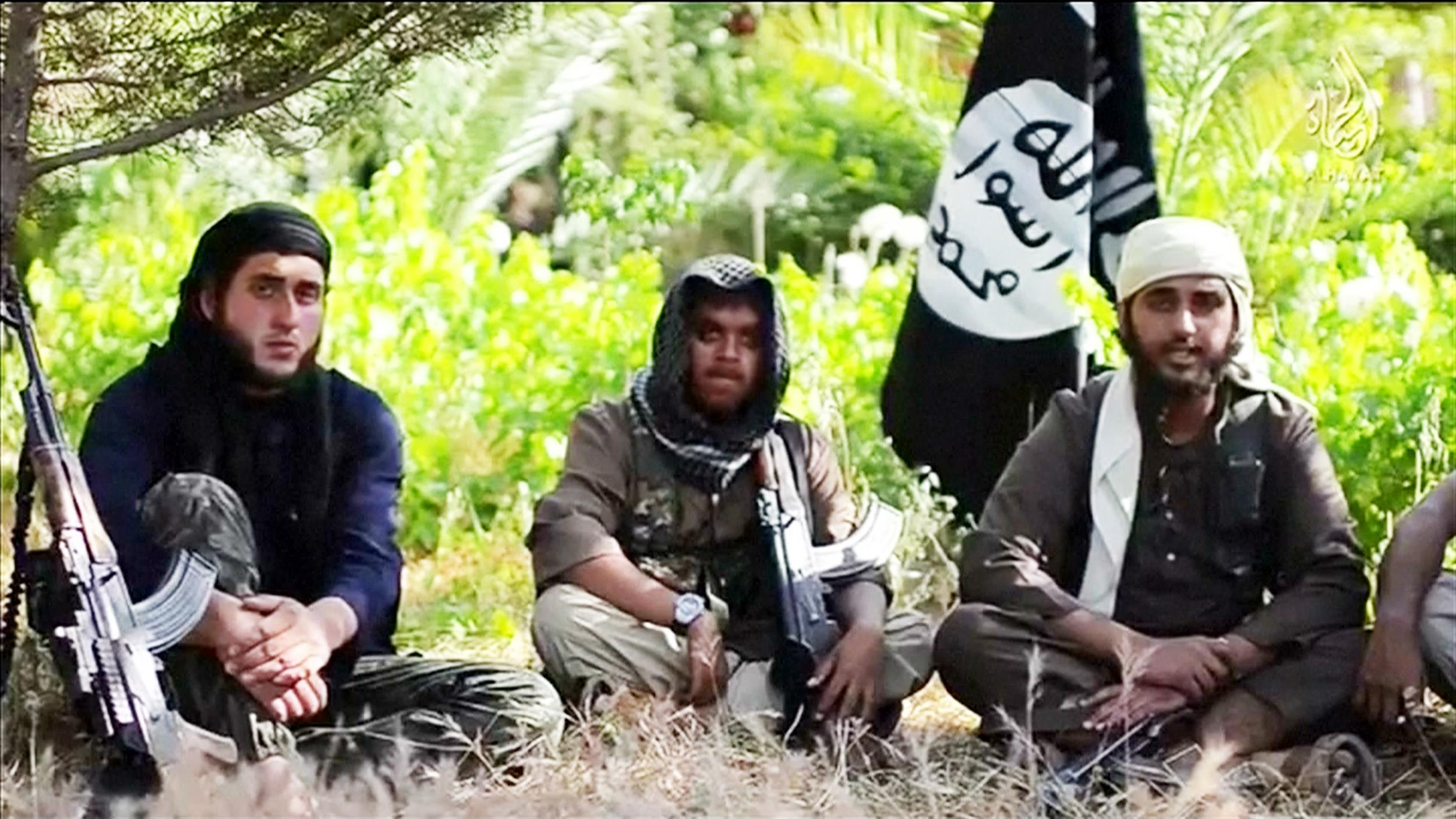 Image: A video shows five rebels, reportedly from Britain and Australia, sitting and holding rifles, with the al-Qaida's black flag flying behind them. NBC News is unable to independently verify the video.
