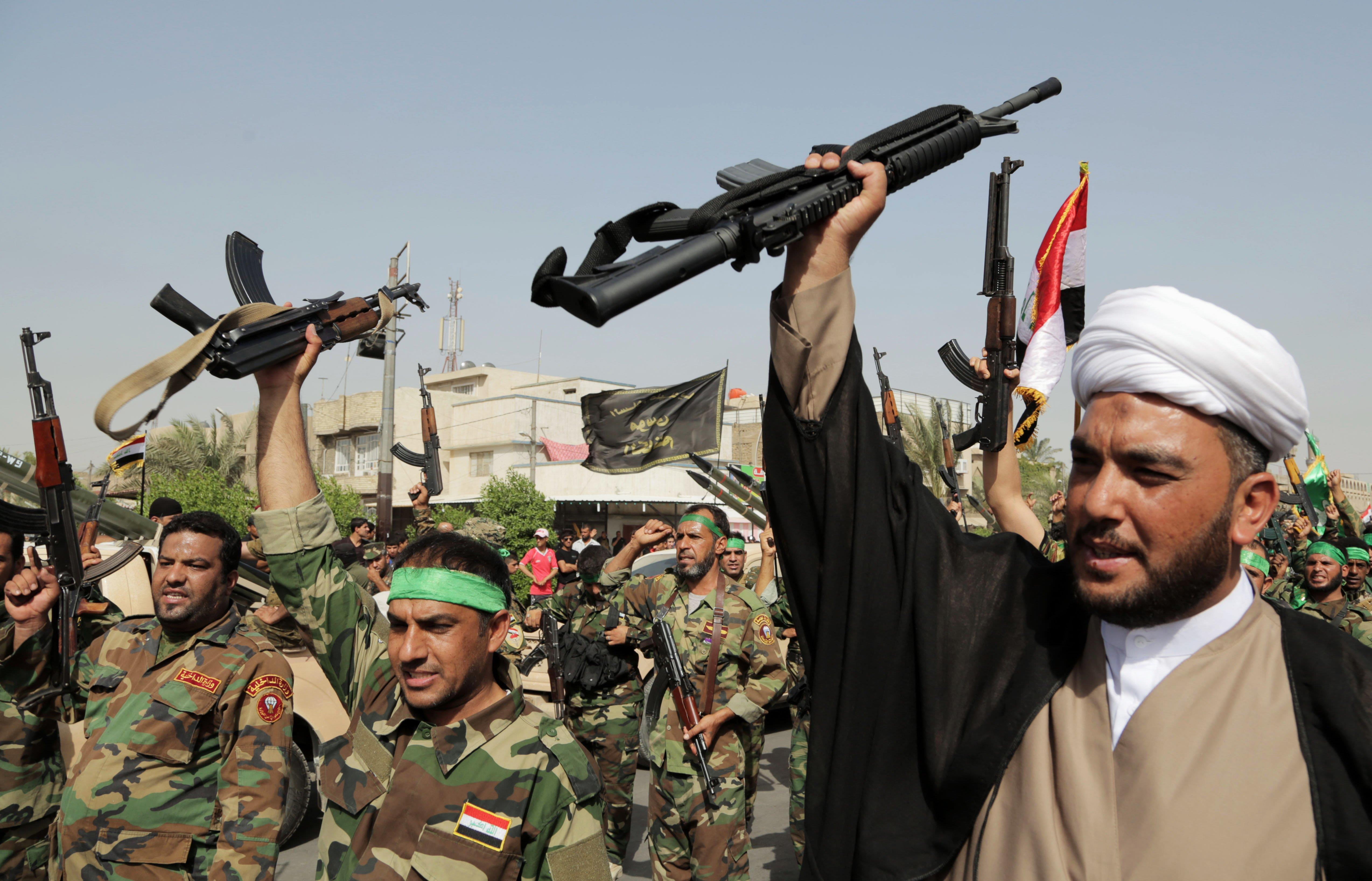 Image: Weapons are raised in Baghdad Saturday during a military parade and demonstration against Islamic militants