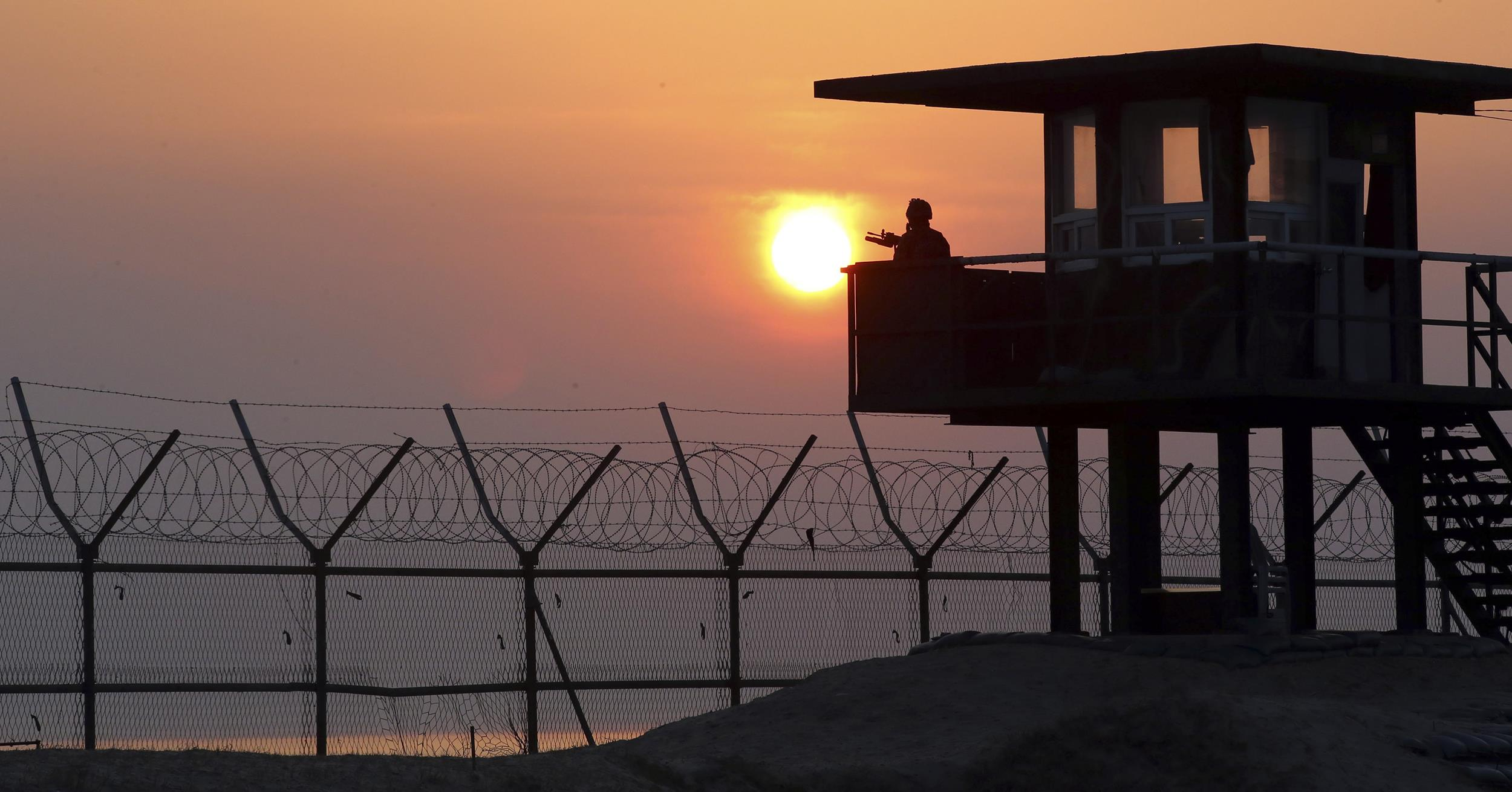 Image: A South Korean soldier guards with his gun at a guard post at sunrise on Baengnyeong Island, South Korea, near the West Sea border with North Korea on April 2