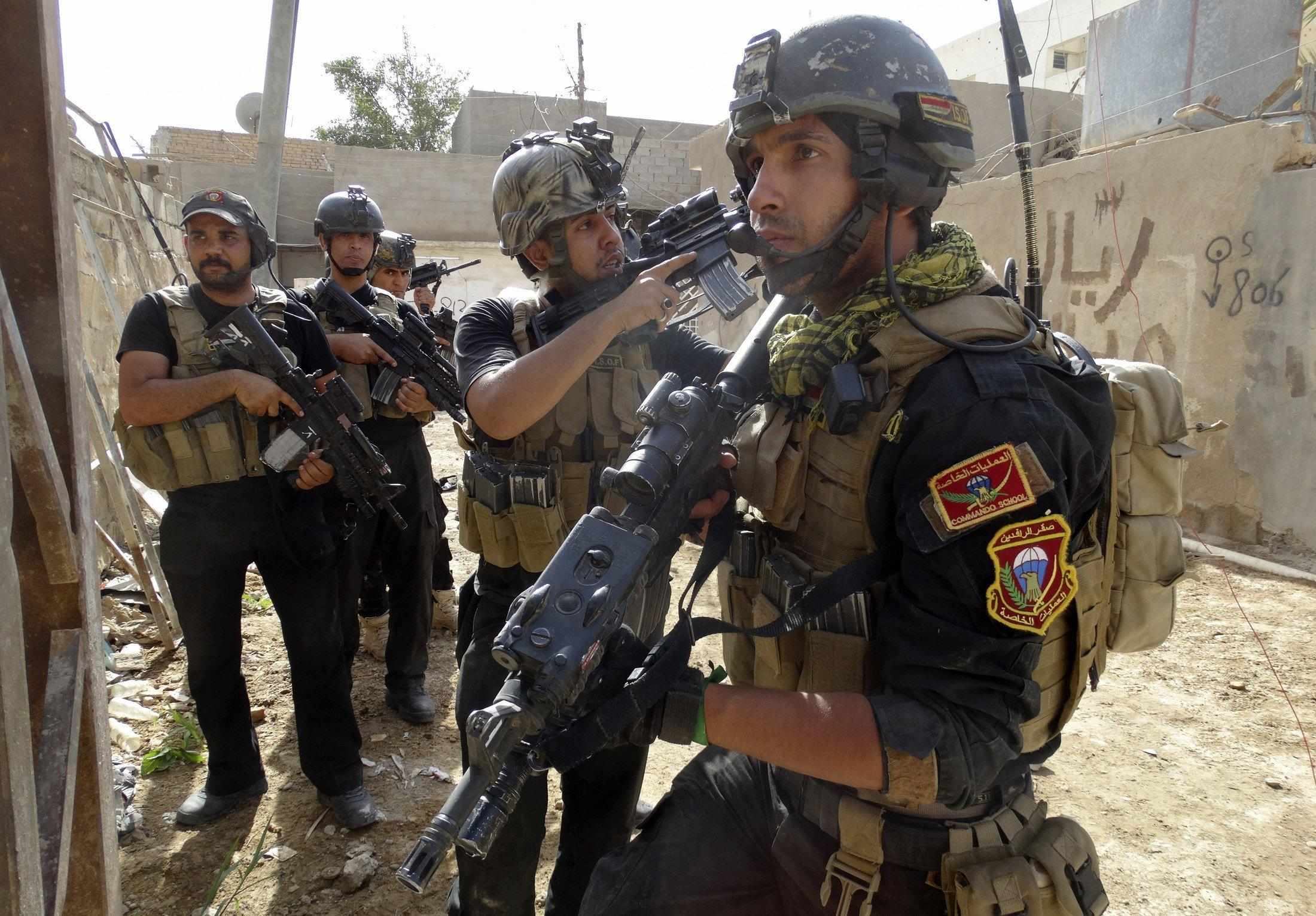 Image: Members of the Iraqi Special Operations Forces take positions during a patrol looking for militants of ISIL, explosives and weapons in Ramadi