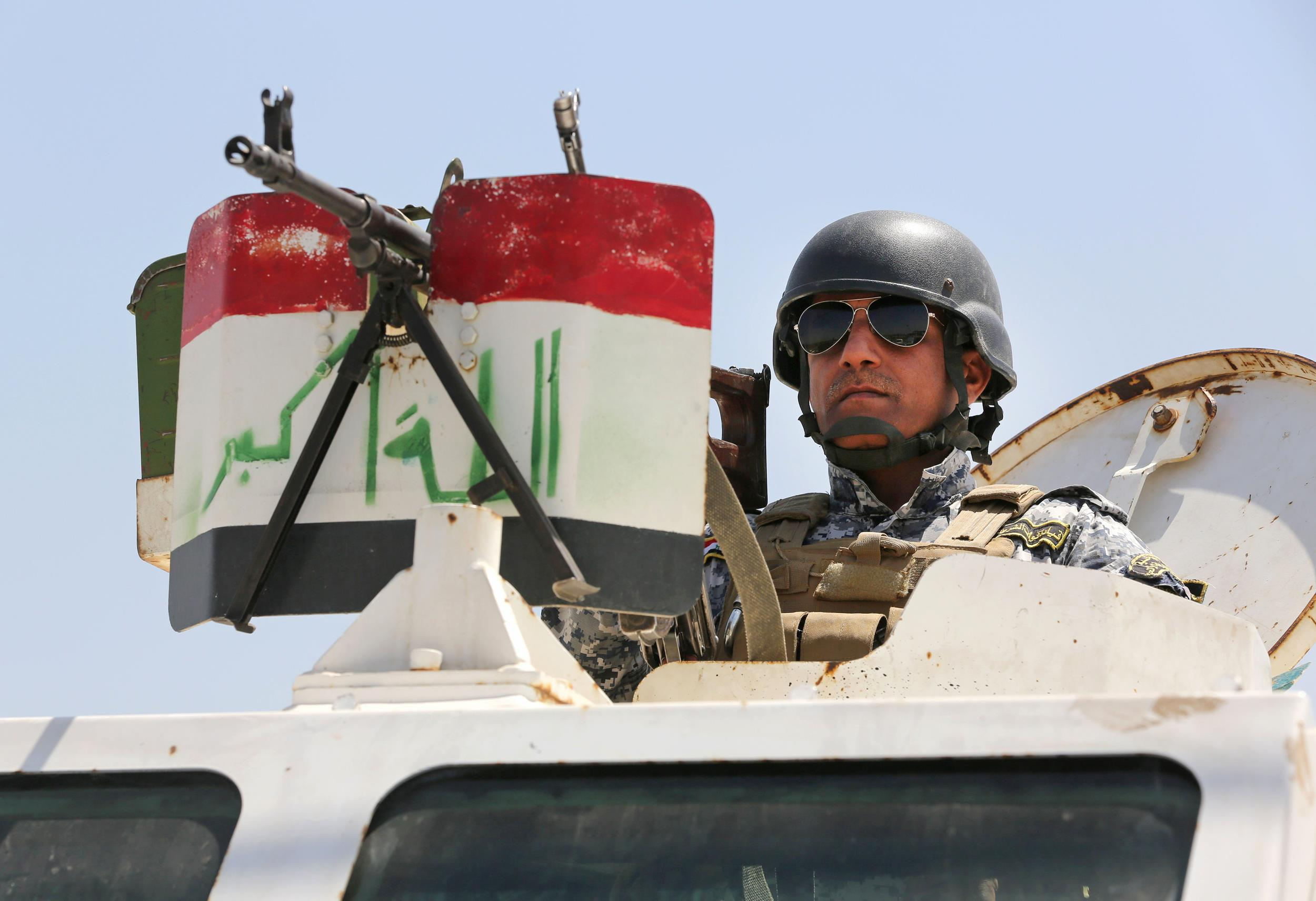 Image: An Iraqi federal policeman stands on top an armored vehicle at a checkpoint in Baghdad on Sunday.