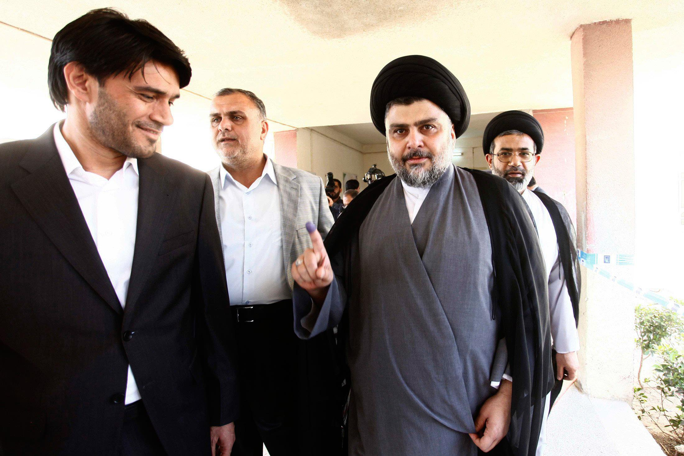 Image: Shiite cleric Muqtada al-Sadr shows his ink-stained finger after voting in parliamentary election at a polling station in Najaf