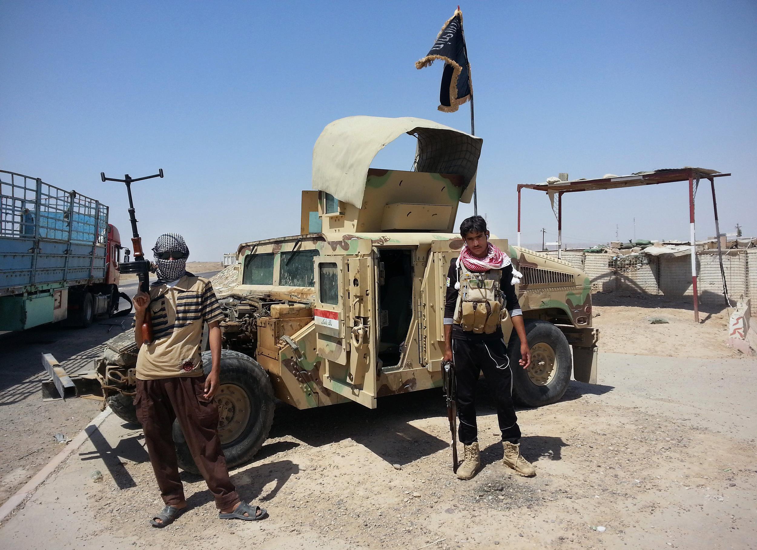 Image: Al-Qaeda inspired militants stand with captured Iraqi Army Humvee
