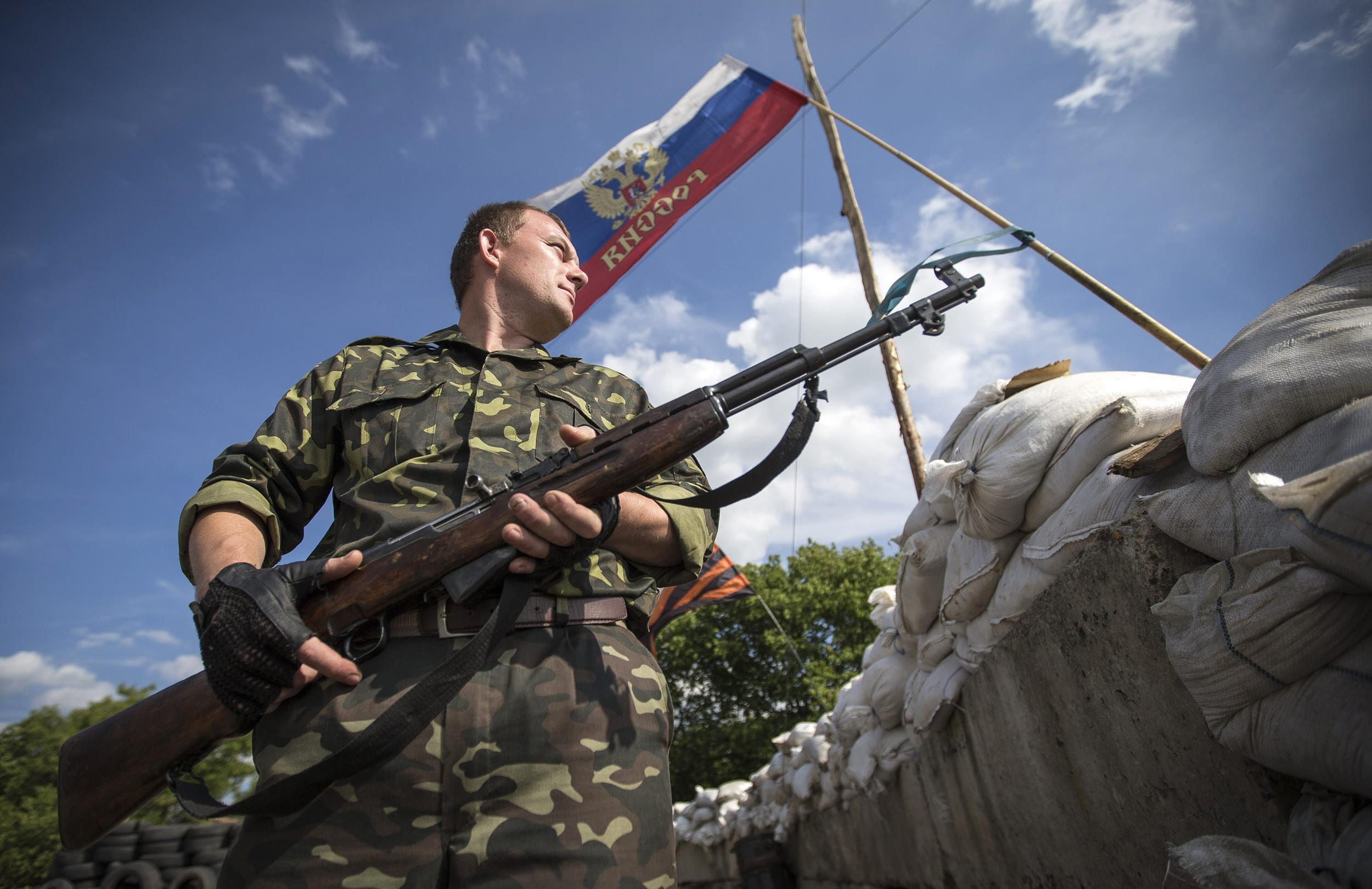 Image: A pro-Russian separatist guards a road checkpoint outside the town of Lysychansk in Luhansk
