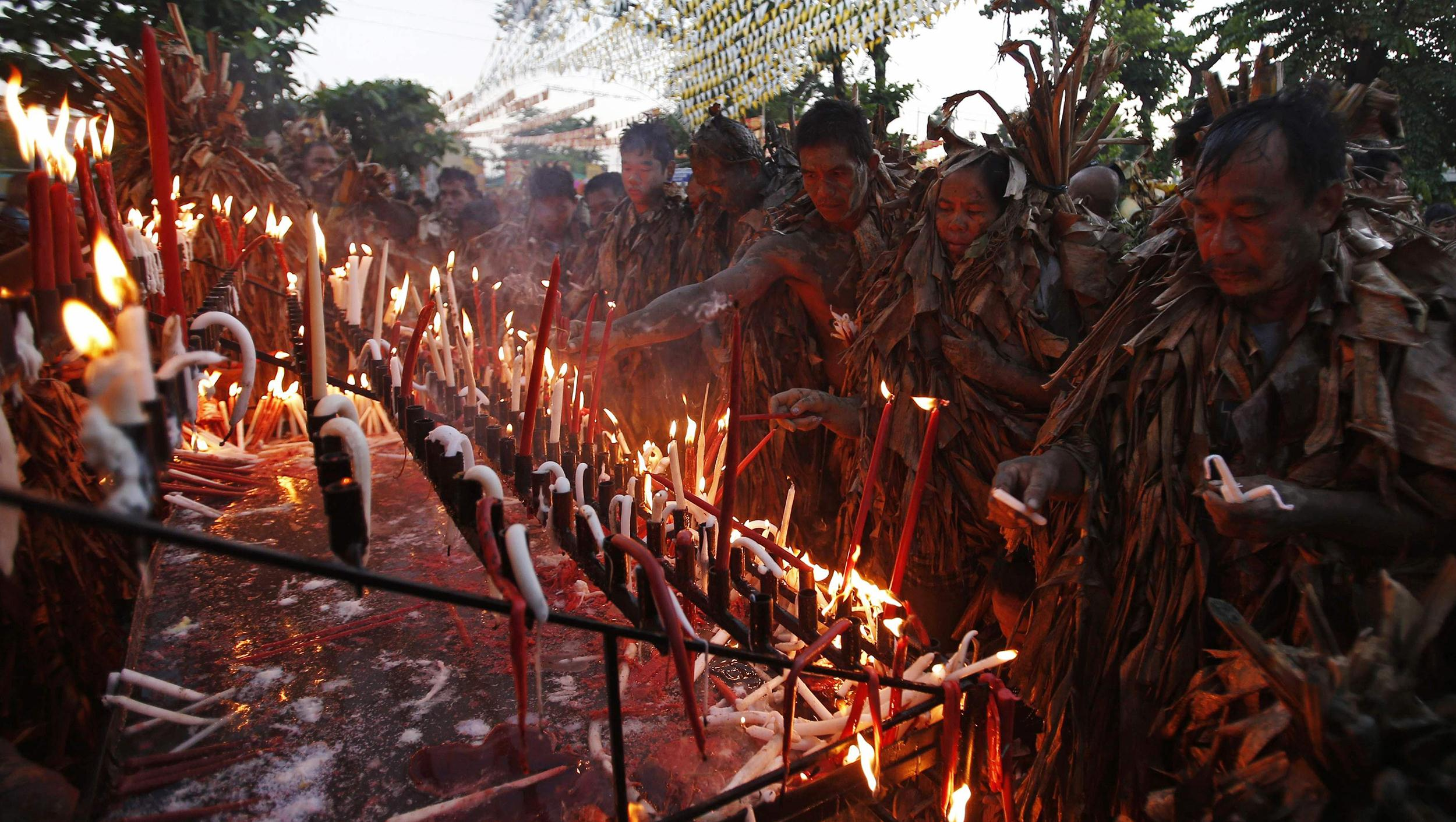 Image: Residents, covered with dried banana leaves and mud, light candles as they take part in a religious ritual known locally as