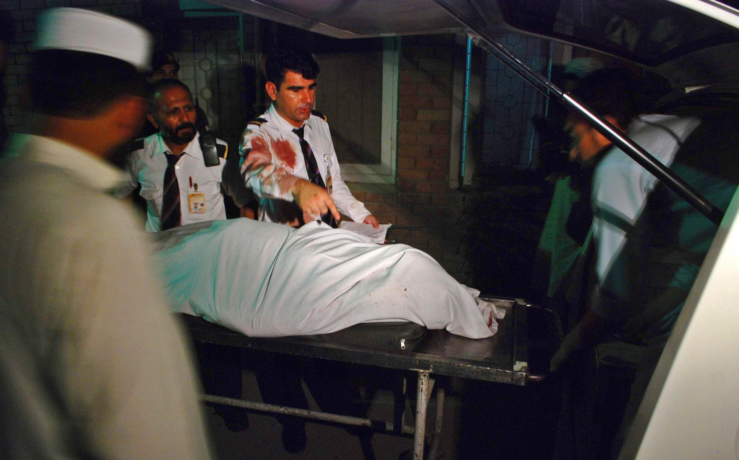 Image: Crew members of a PIA plane are seen beside the body of a woman who was killed on board their aircraft, at a hospital in Peshawar