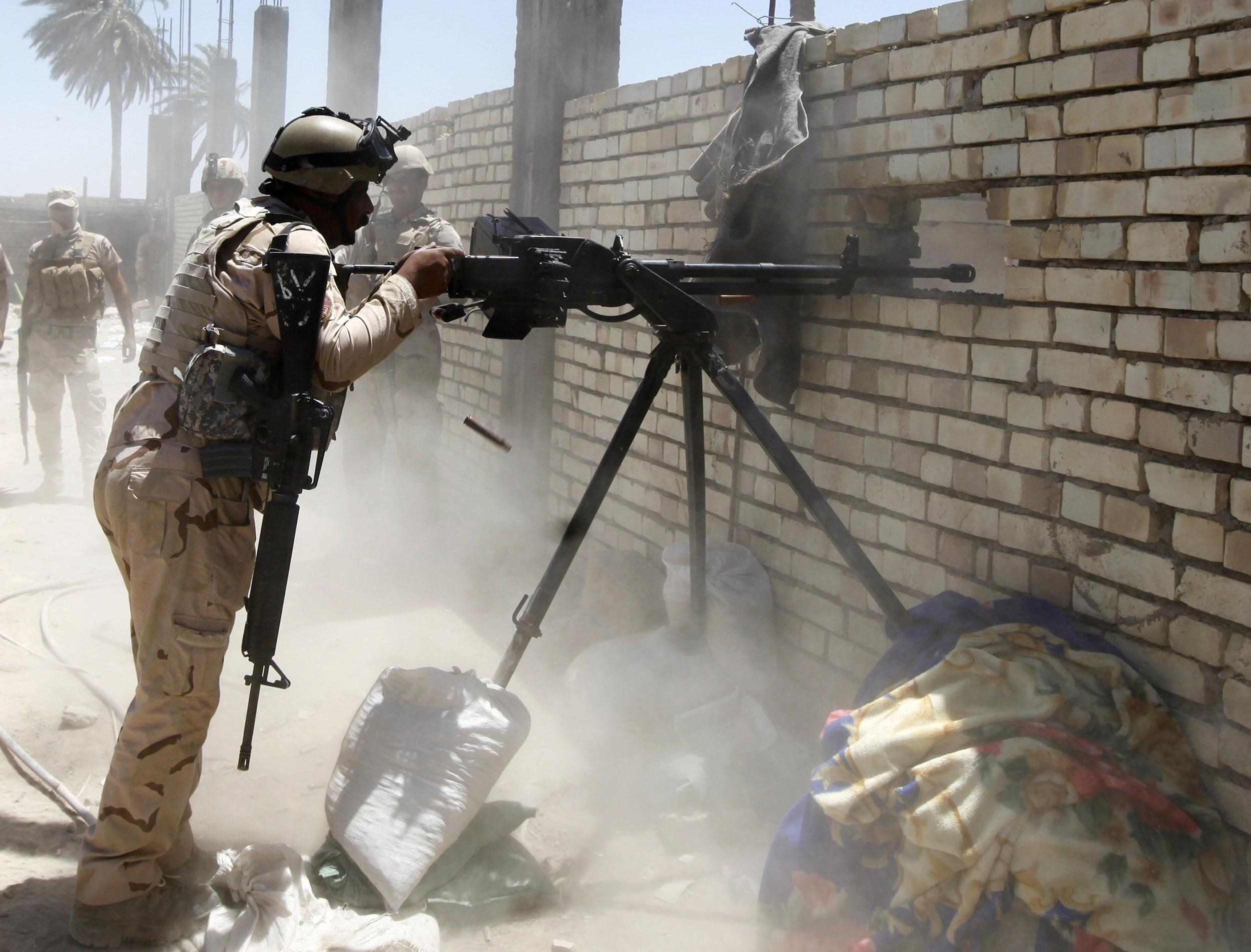 Image: A member of the Iraqi security forces opens fire during clashes with the ISIL, west of Baghdad