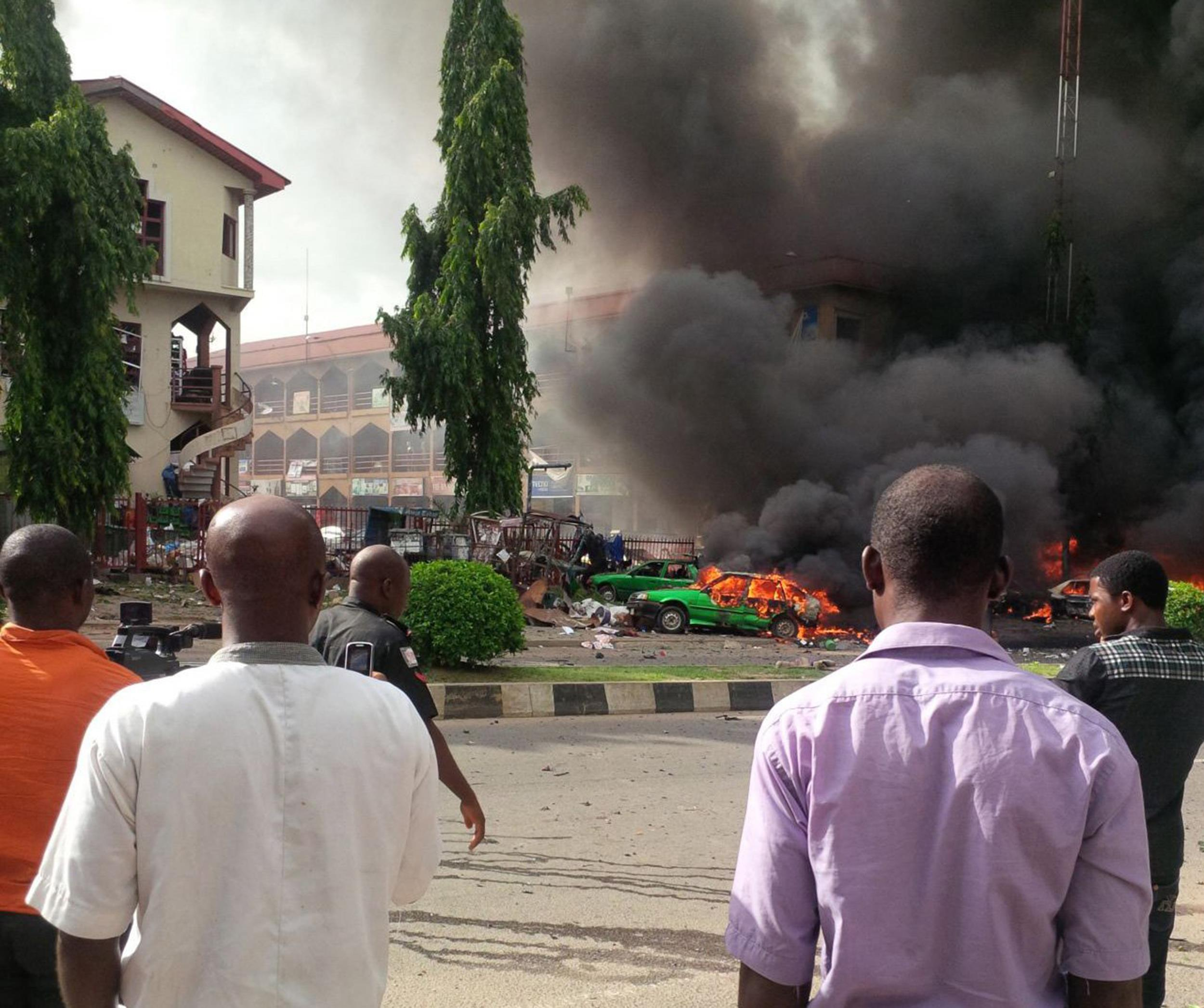 Image: People watch as smoke fills the sky, after an explosion, at a shopping mall on June 25, in Abuja, Nigeria