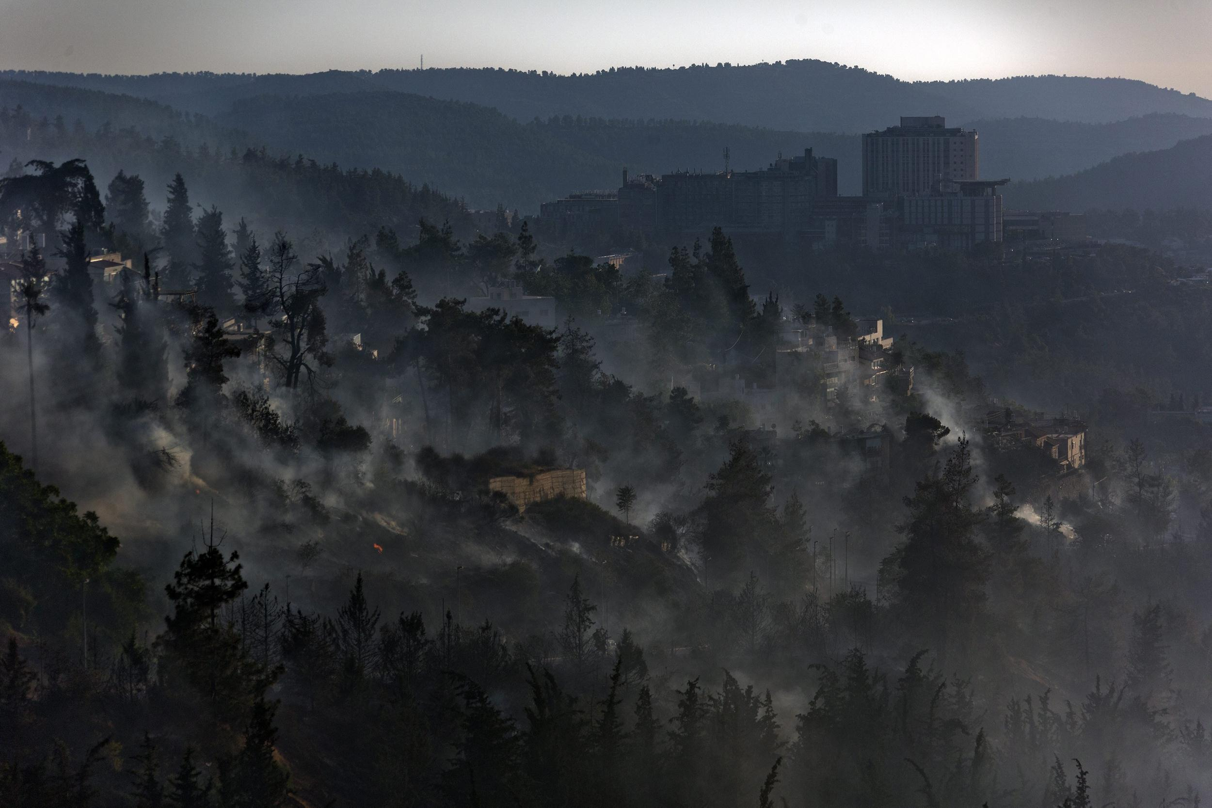 Image: A general view of Jerusalem looking down towards the the village of Ein Keren as a large fire burns in Jerusalem Forest, Israel, on June 25