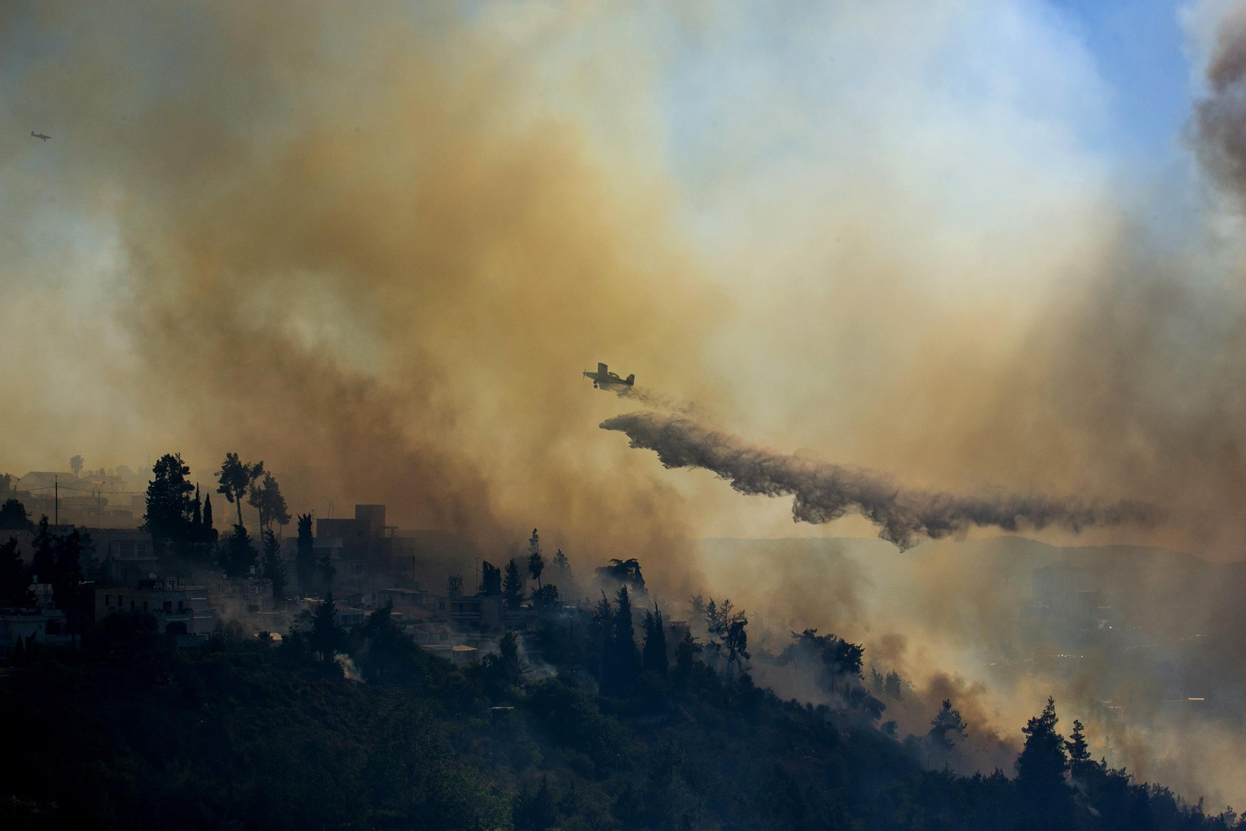 Image: A plane drops fire retardant to extinguish fire burning in the forest in Jerusalem, Israel on June 25.
