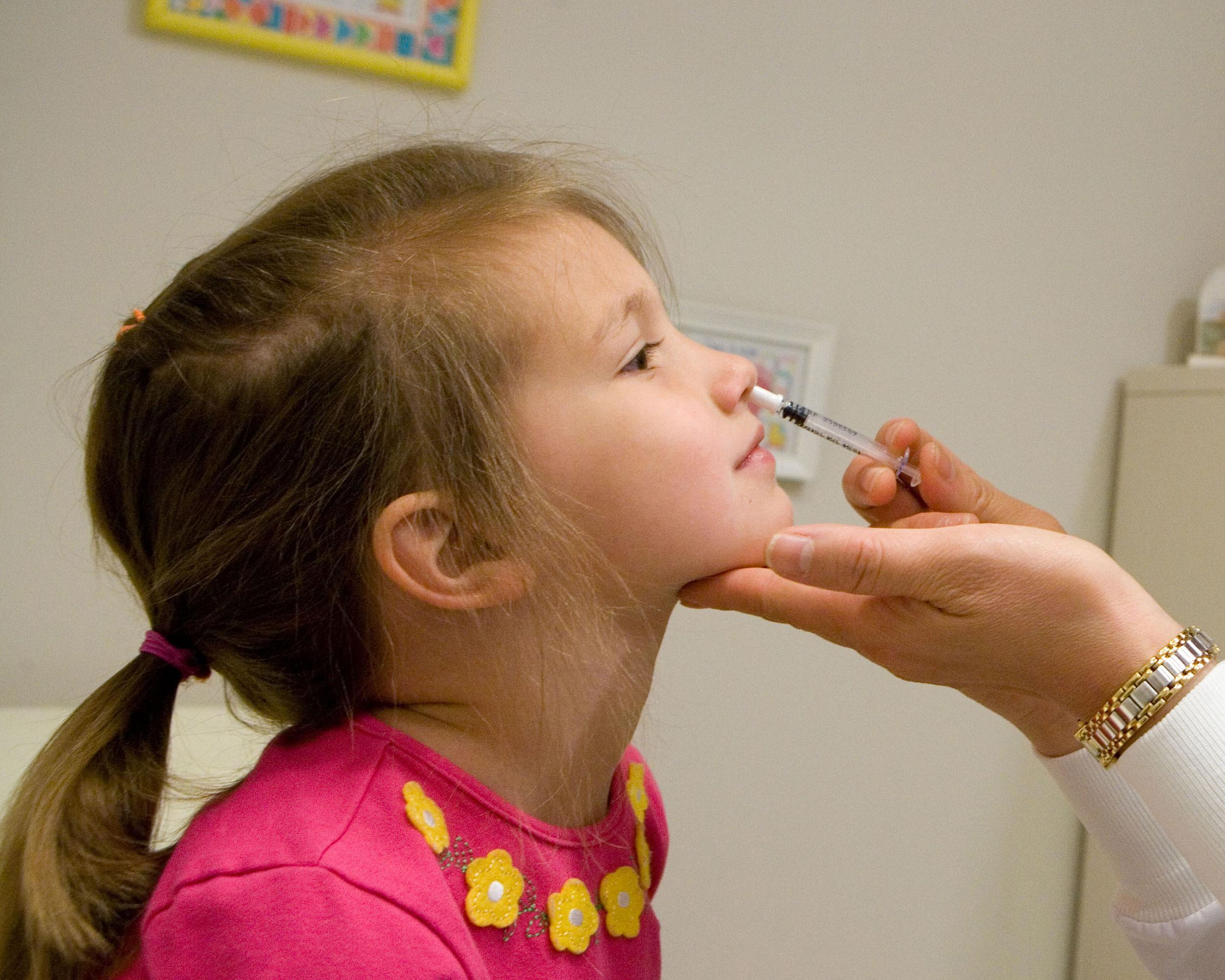 Image: A healthcare provider uses an empty sample sprayer to demonstrate how to administer FluMist to a preschooler.