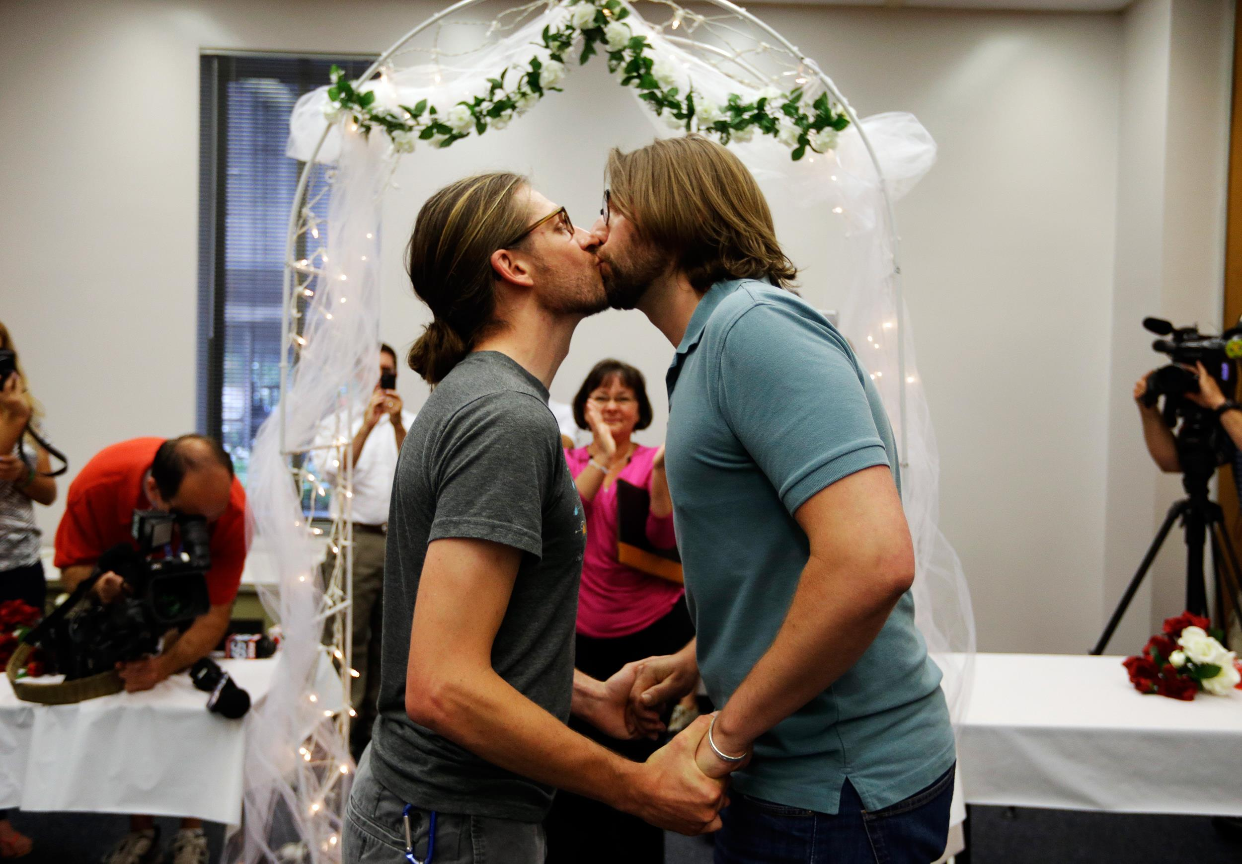 Image: Jake Miller, 30, and Craig Bowen, 35, right, kiss after being married by Marion County Clerk Beth White, center, in Indianapolis