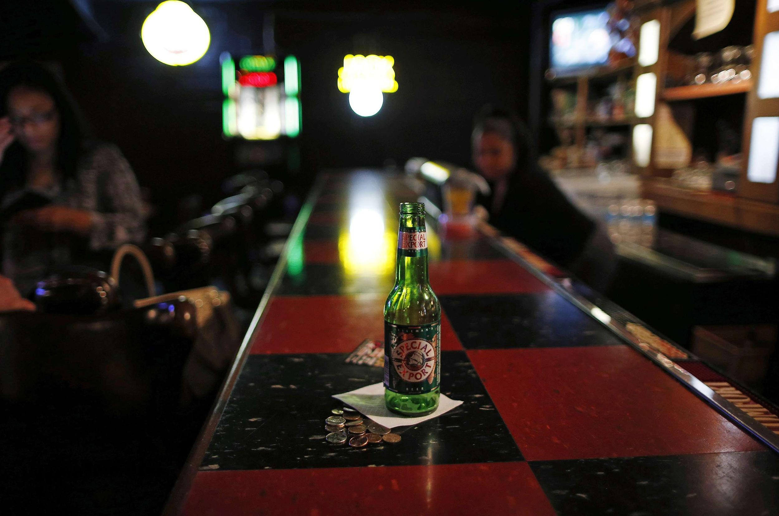 Image: An empty beer bottle is seen on the bar at the Checkerboard Lounge in Chicago