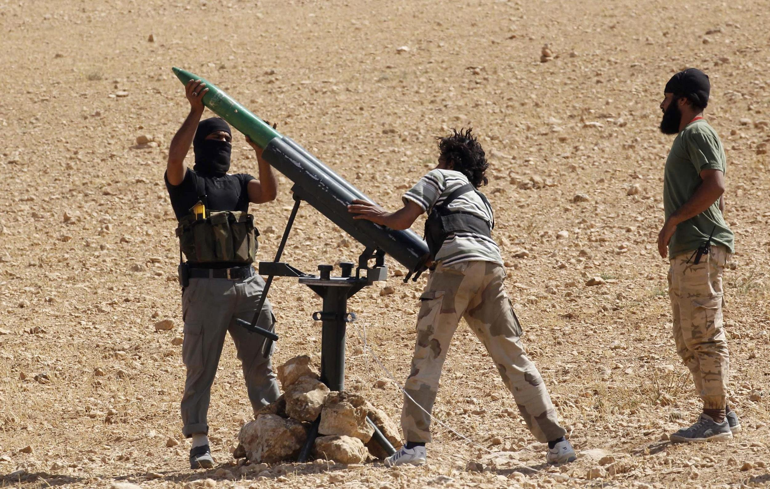 Image: Free Syrian Army fighters prepare a rocket before firing it