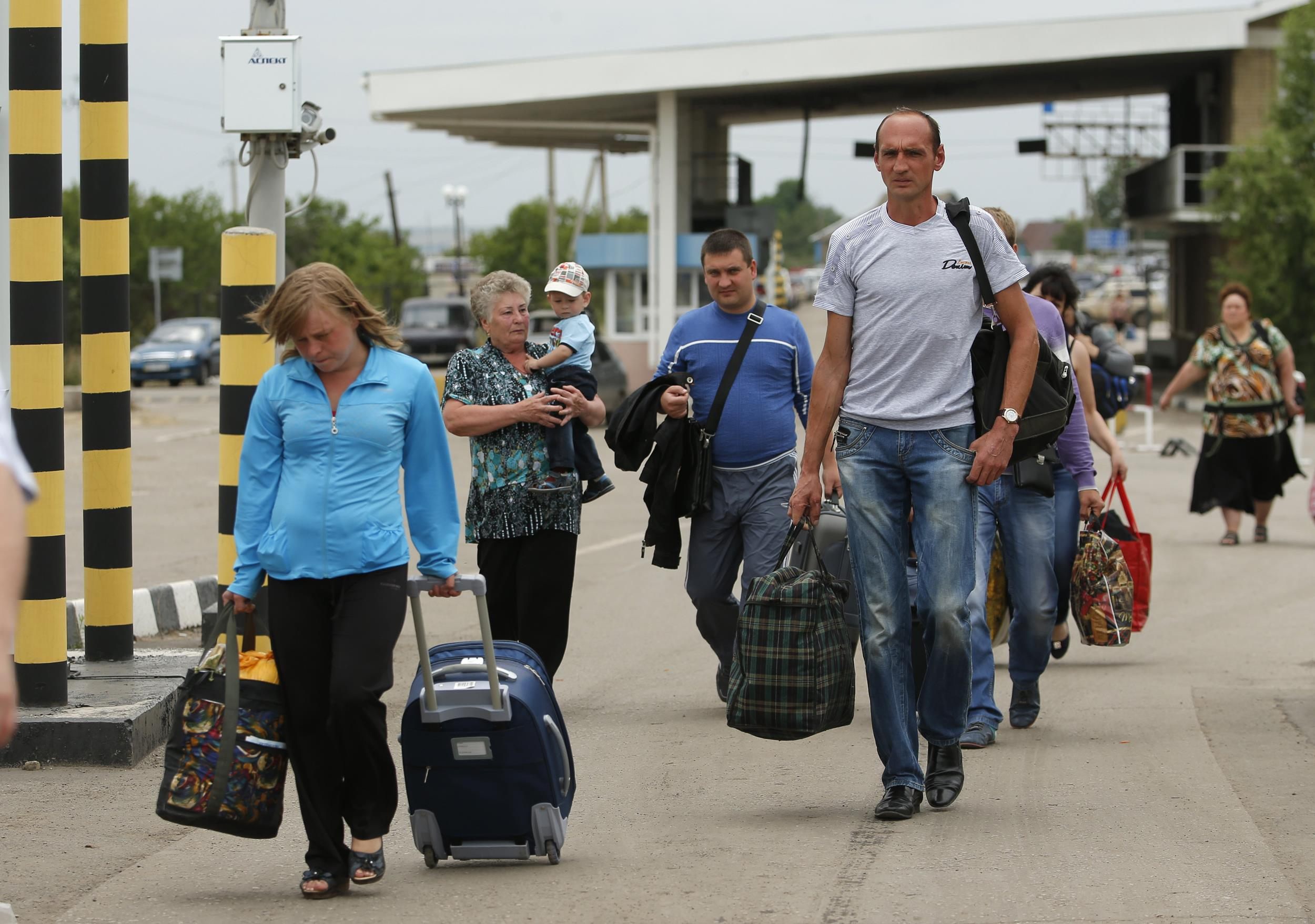 Image: People carry their belongings as they walk to cross the border into Russia at the Ukrainian-Russian border checkpoint in Izvaryne, Luhansk region, eastern Ukraine Thursday.