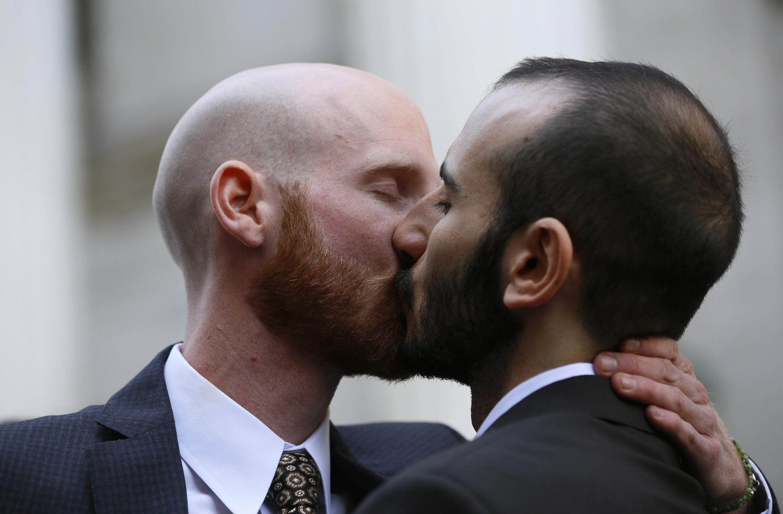 Image: Lead plaintiffs kiss outside the courthouse after a federal appeals court heard oral arguments on a Utah state law forbidding gays and lesbians from marrying in Denver