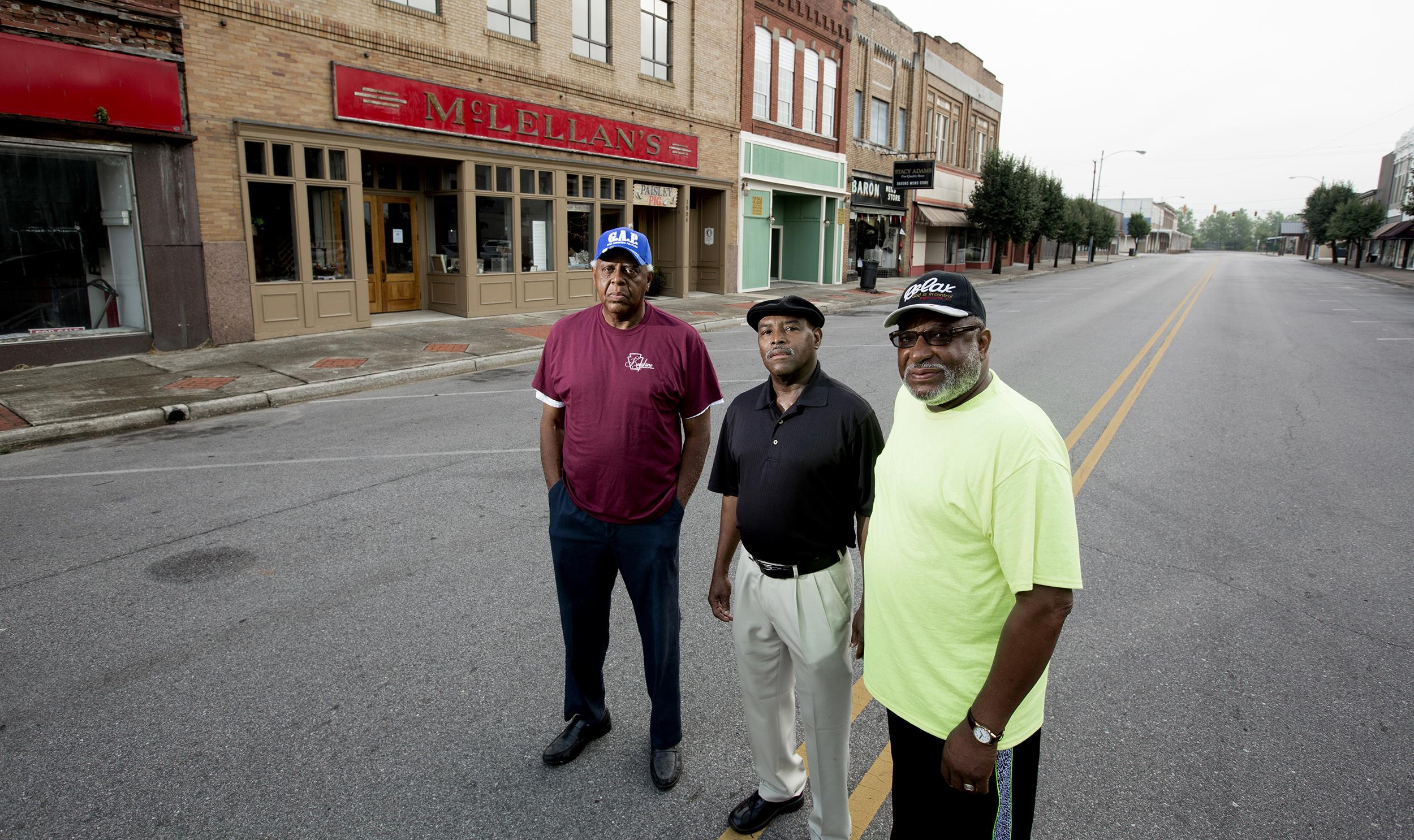 Image: Herman Williams , Desmond Wright  and Albert Shade stand outside of now the closed McLellan's department store almost fifty years after they staged a sit-in there to protest the whites-only lunch counter.