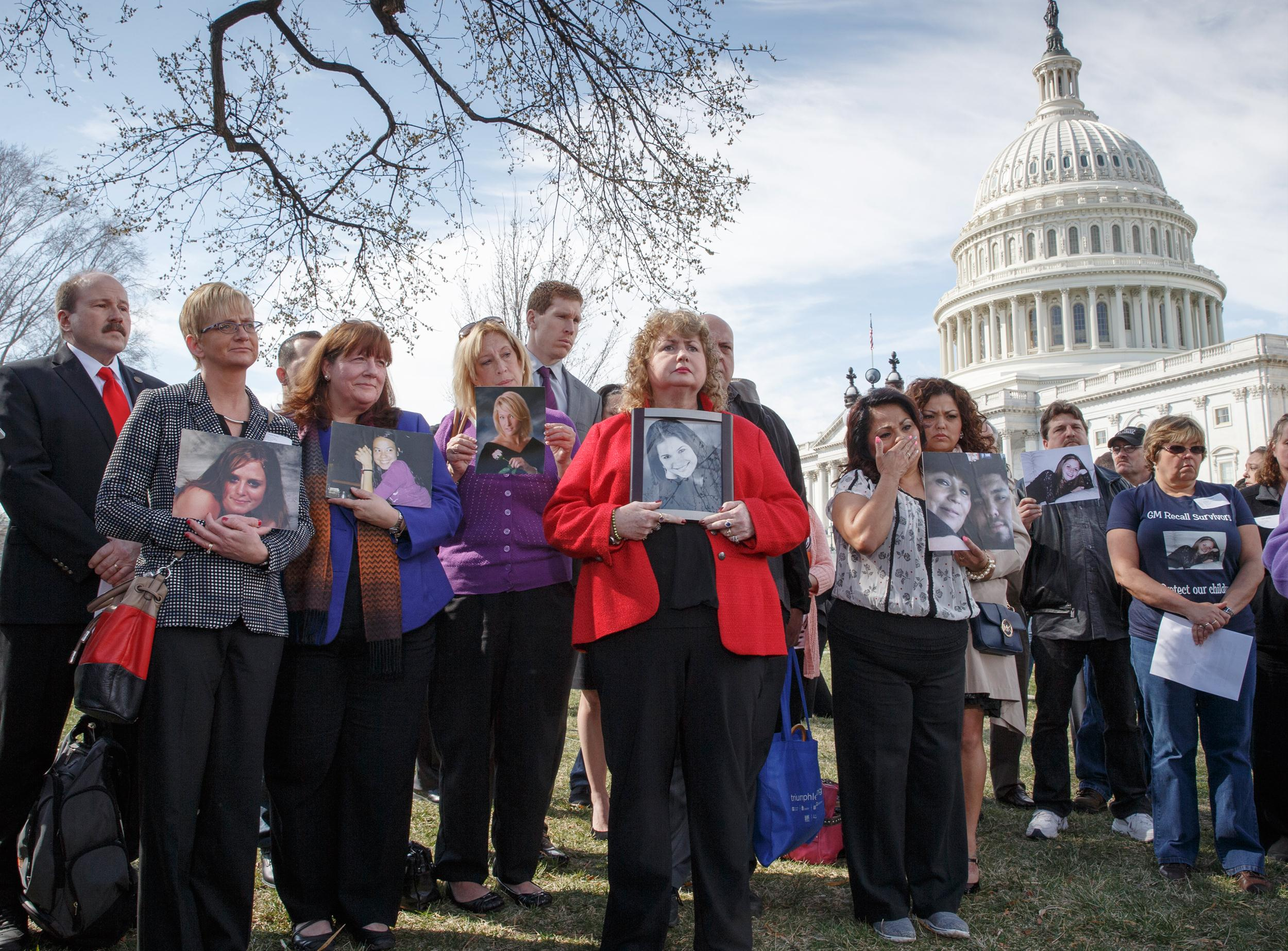 Image: Families of victims of a General Motors safety defects in small cars hold photos of their loved ones