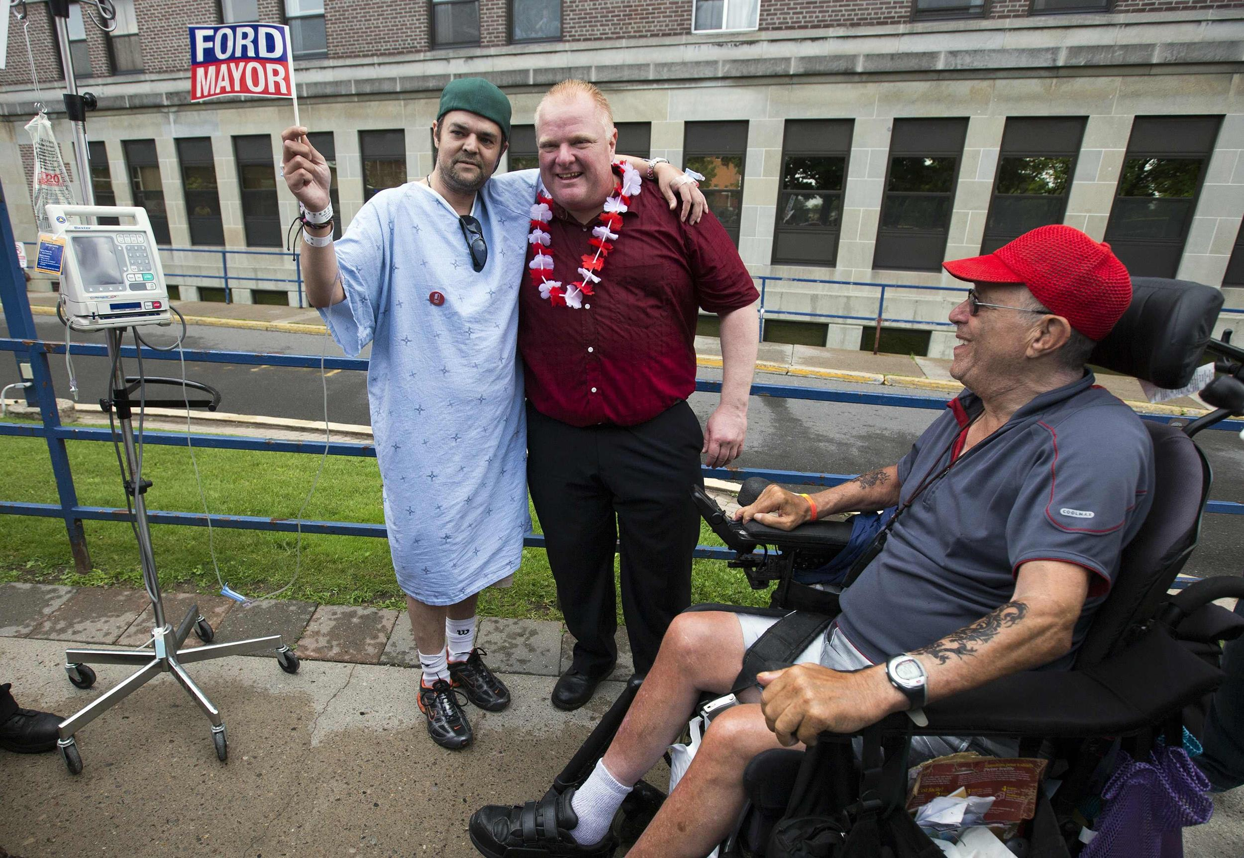Image: Toronto Mayor Rob Ford poses with a hospital patient as he takes part in parade in his first public appearance since returning from a rehabilitation clinic in Toronto
