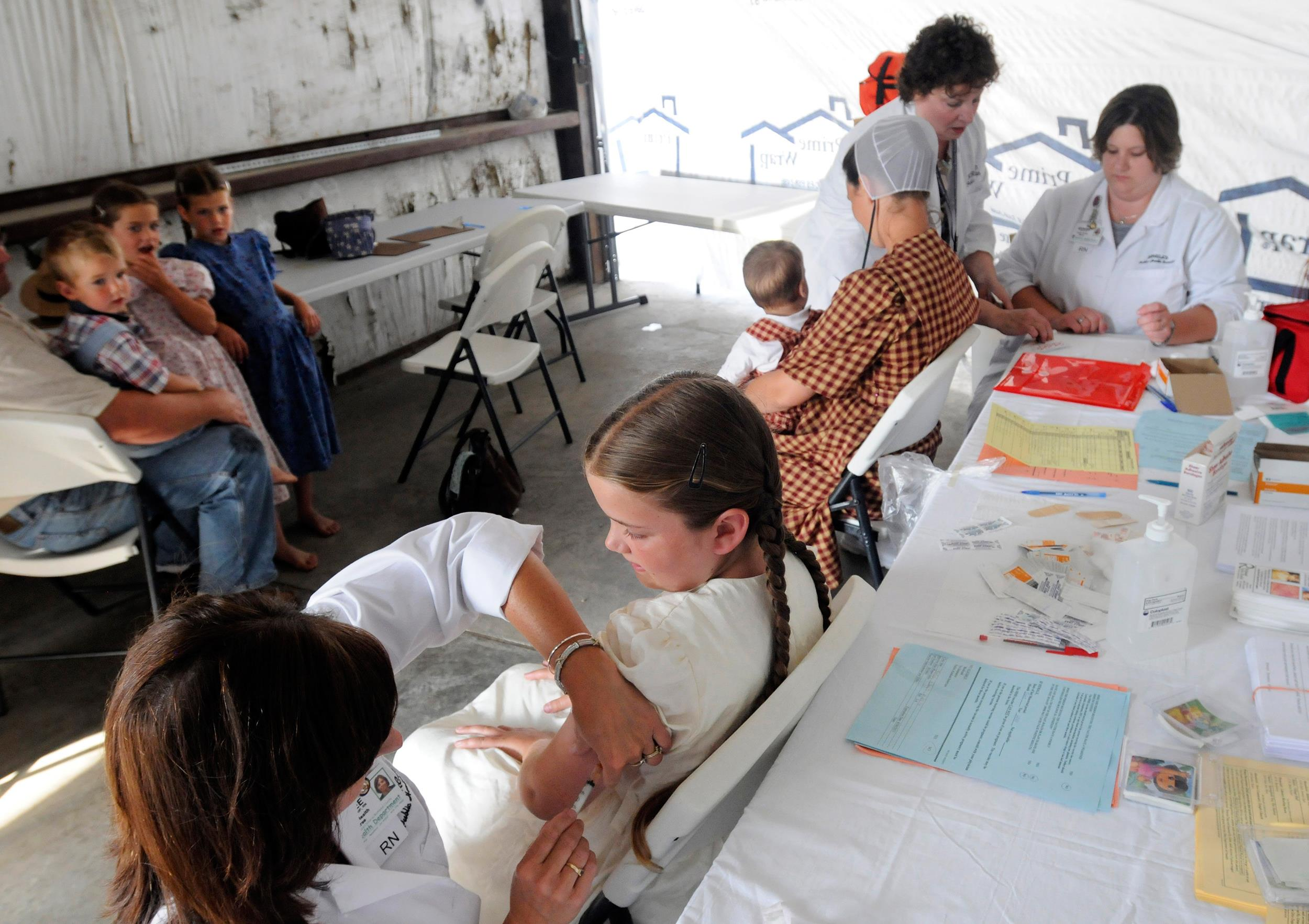 Image: An Amish girl gets a Measles, Mumps, and Rubella vaccination.