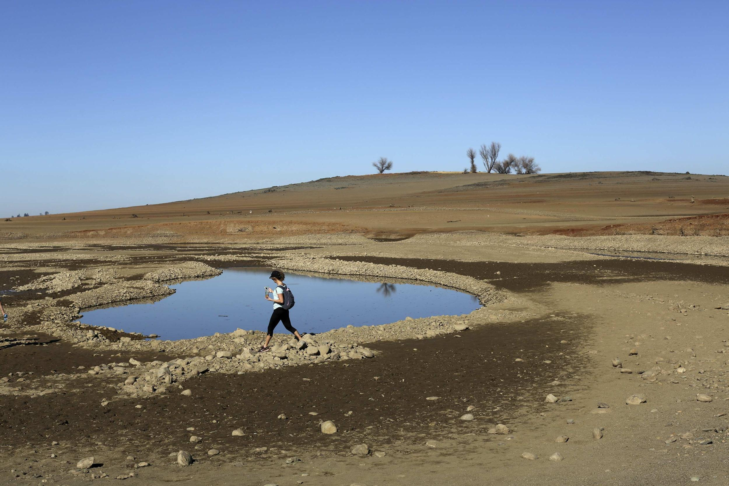 A visitor walks near the receding waters at Folsom Lake, in Folsom, California.