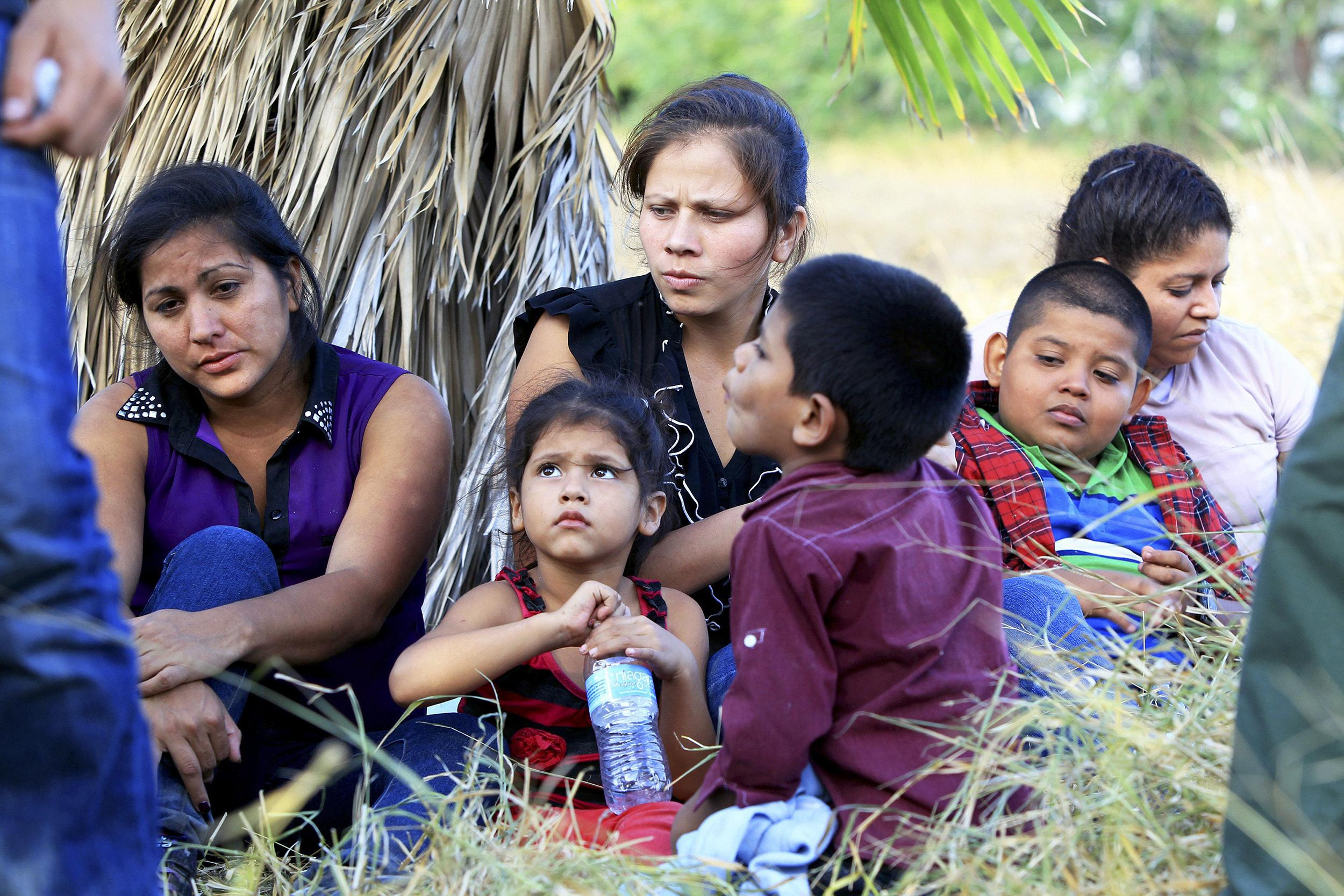 Image: A group of 22 migrants, mostly women and children from Honduras and Guatemala, in custody just after crossing the Rio Grande near McAllen, Texas.