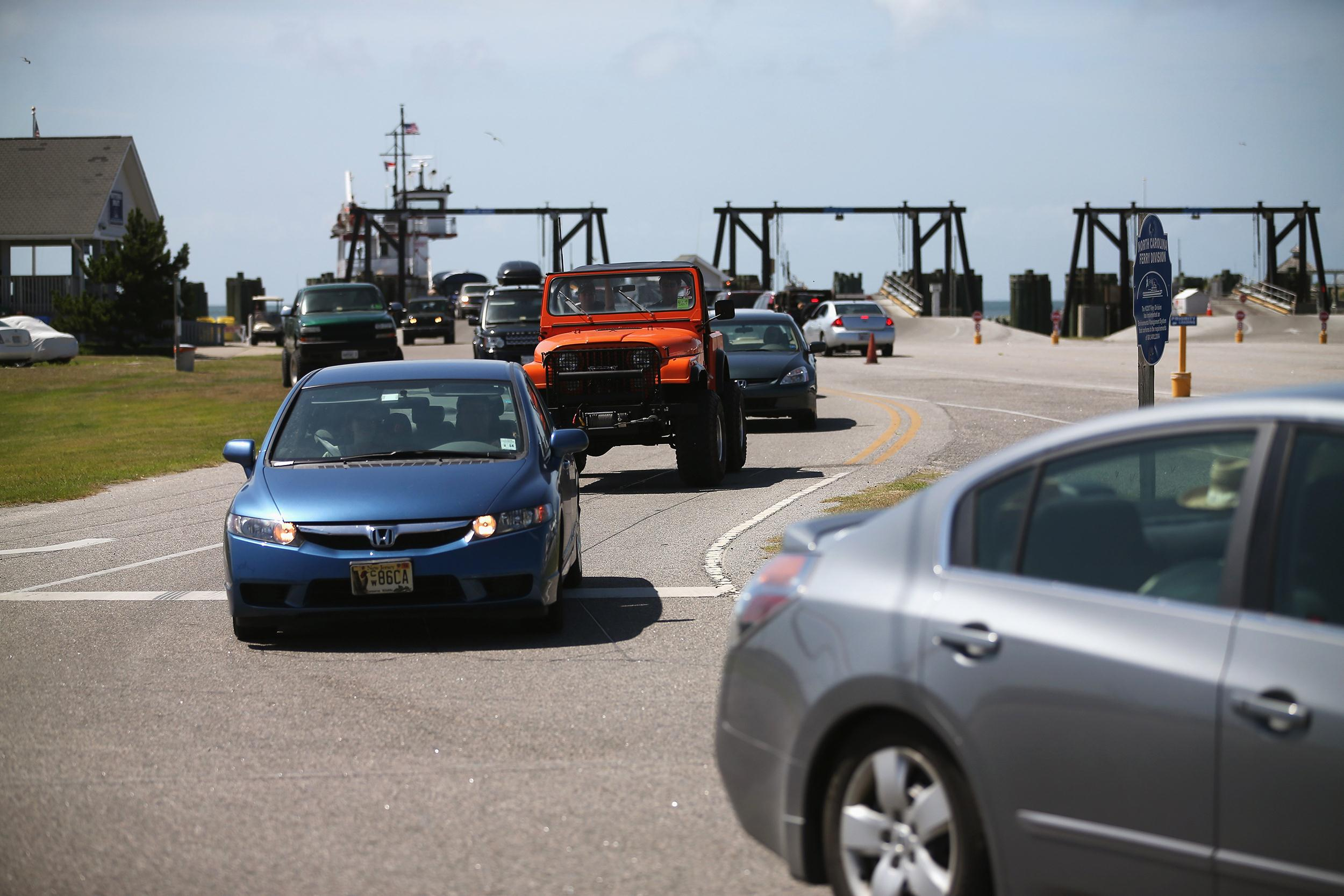 Image: Vehicles drive off the ferry from Ocracoke Island which officials have called for a voluntary evacuation