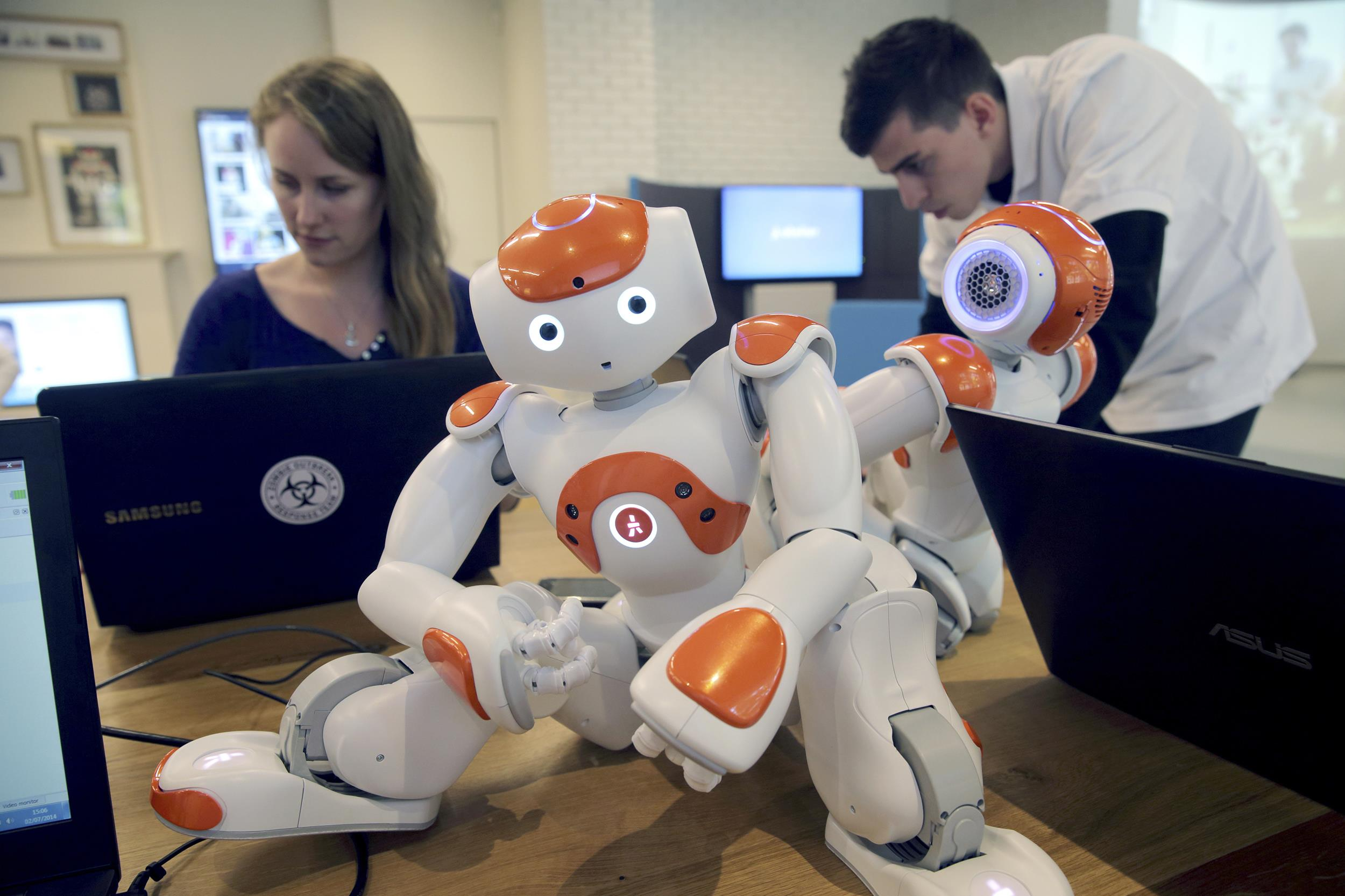 Image: Visitors and staff work on computers next to humanoid robots