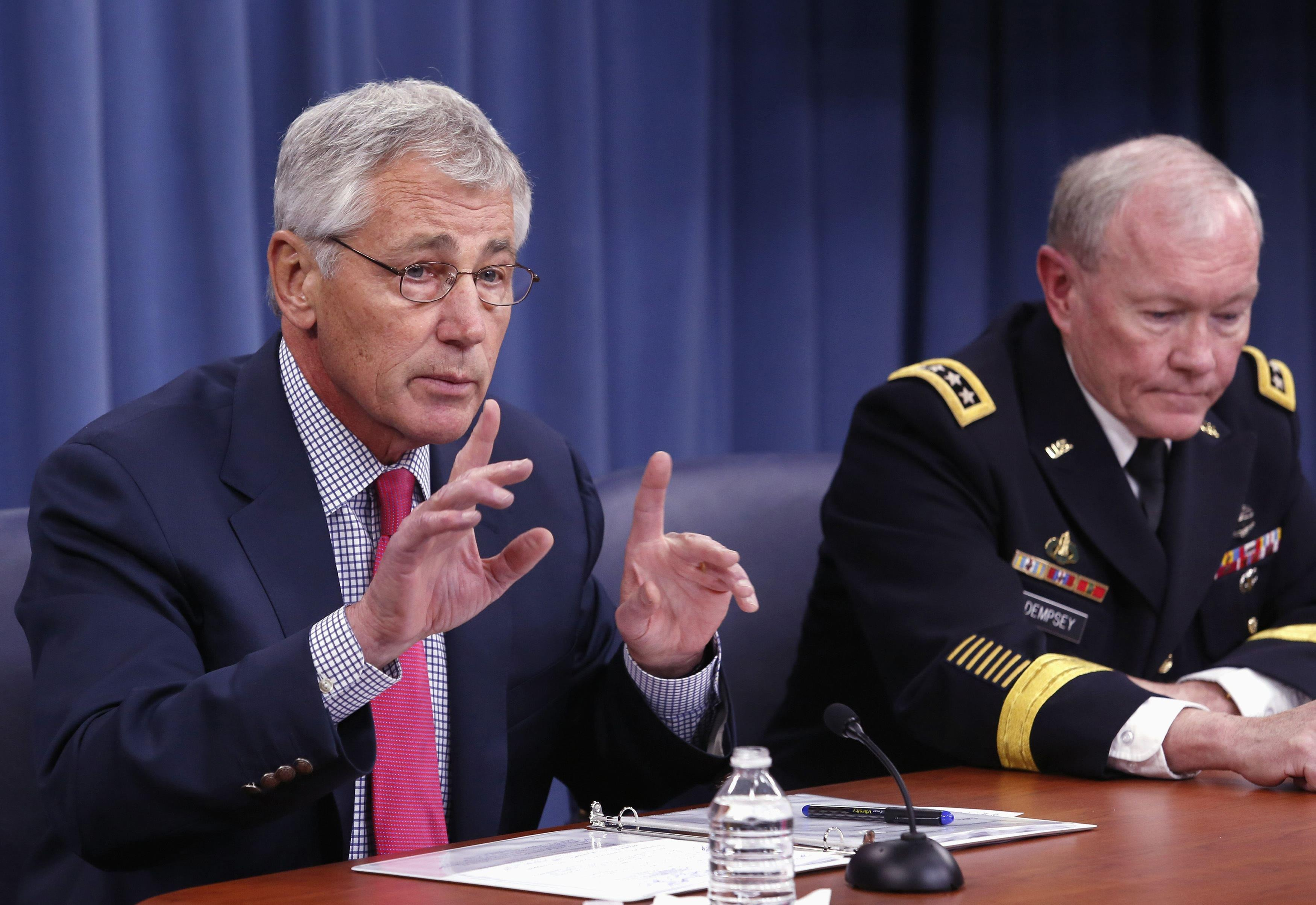 Image: U.S. Secretary of Defense Chuck Hagel speaks next to Chairman of the Joint Chiefs of Staff General Martin Dempsey during a media briefing at the Pentagon in Washington