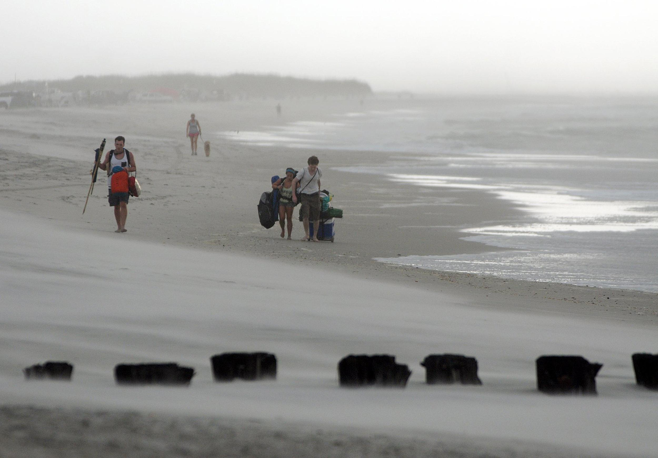 Image: Clouds and rains move in as beachgoers leave Freeman Park at the north end of Carolina Beach, N.C.