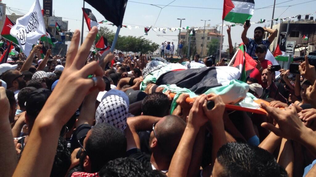 Crowds of mourners carried the body of a slain Palestinian through the streets of east Jerusalem on Friday,