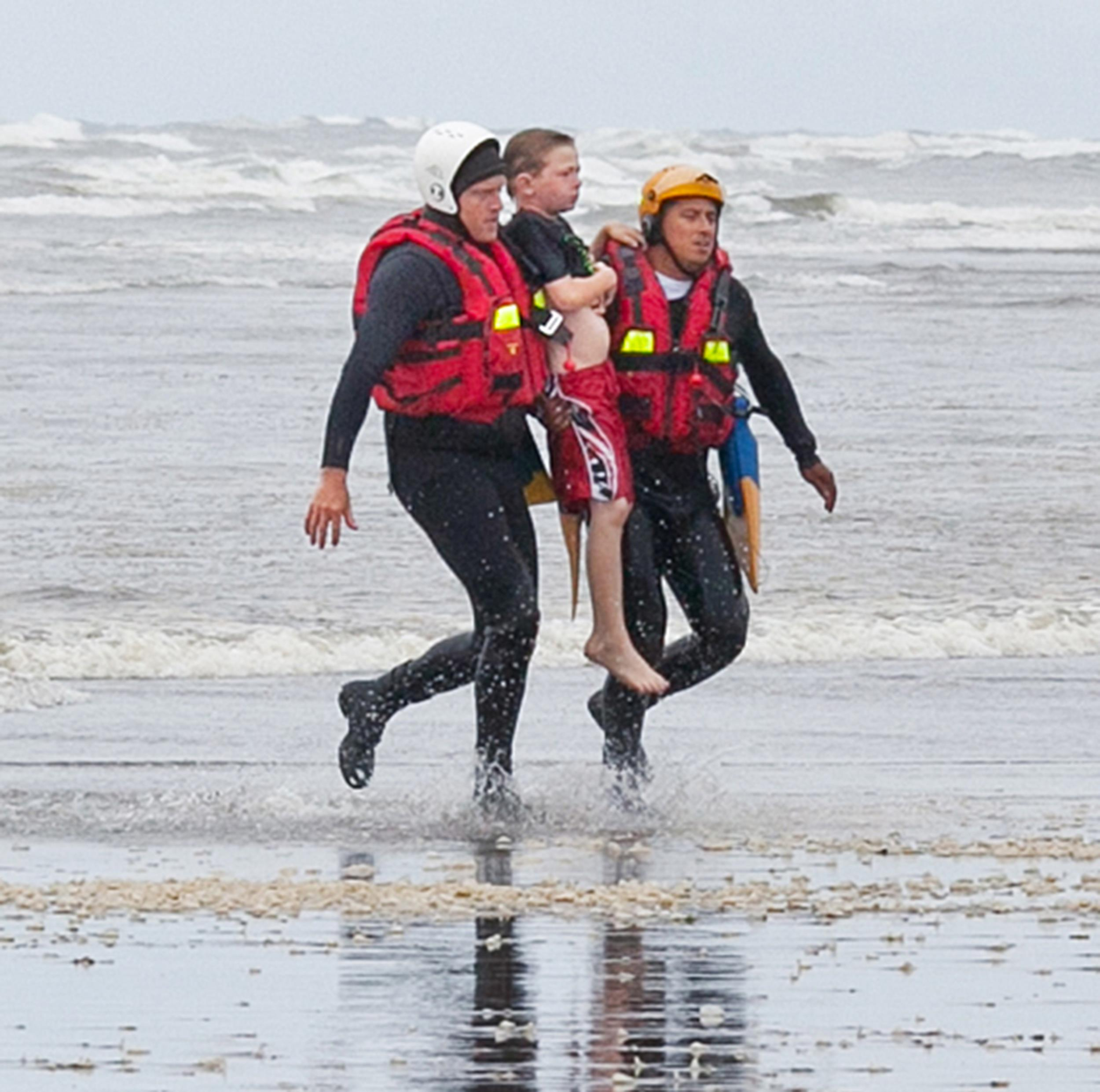 Image: Surf rescue swimmers Julez Orr and Eddie Mendez carry an 11-year-old boy to the shore at Long Beach, Wash.