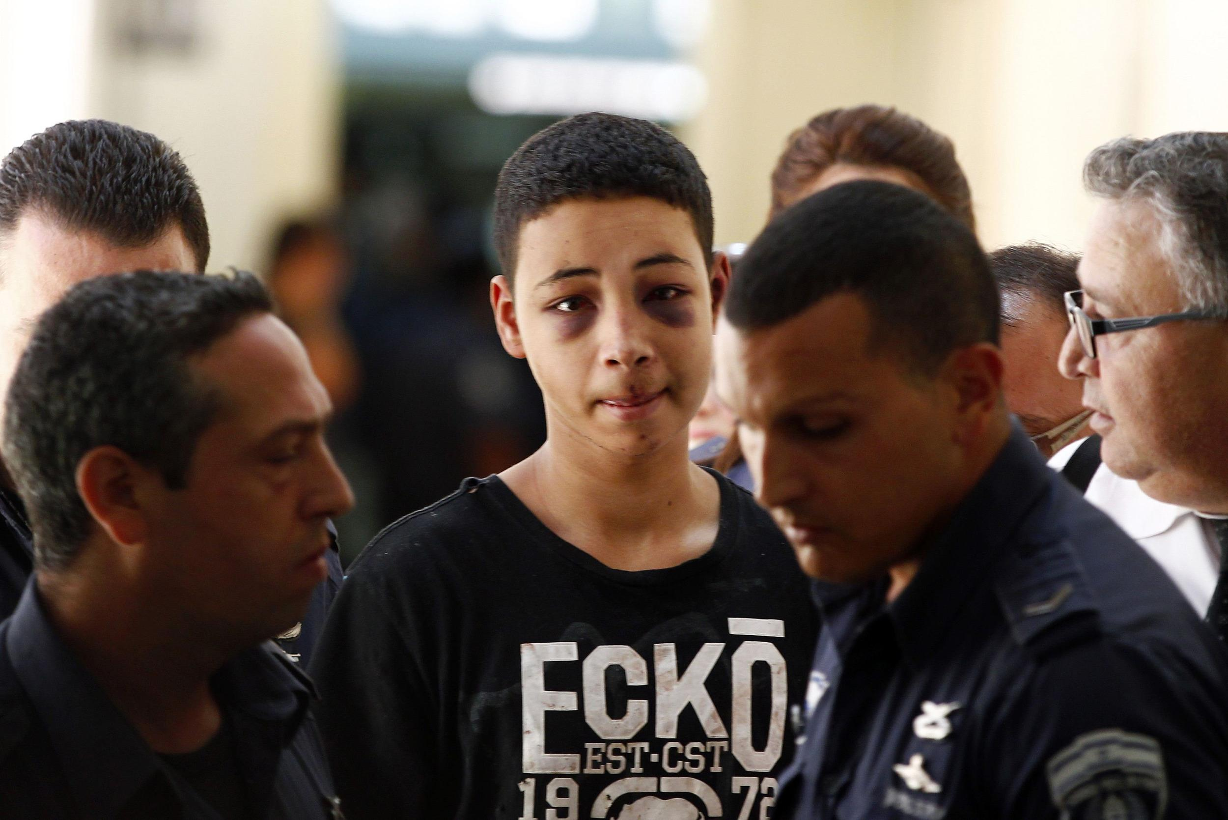 Image: Tariq Khdeir, an American of Palestinian descent, is escorted by Israeli prison guards during an appearance at Jerusalem magistrate's court