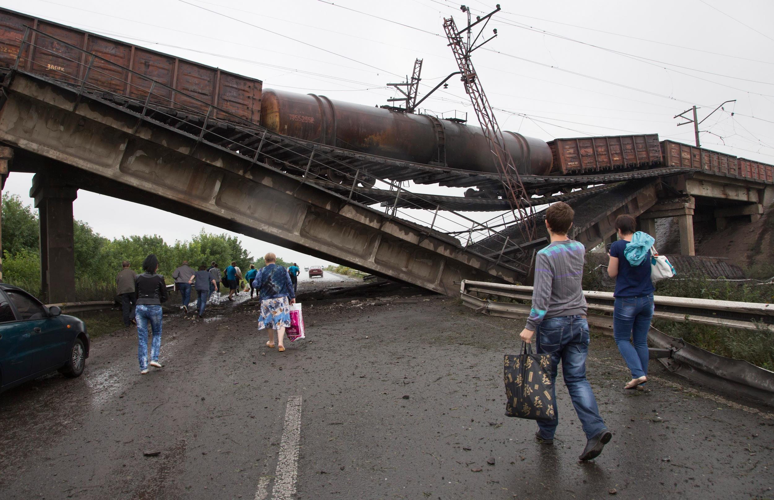 Image: People walk under a destroyed railroad bridge over a main road leading into the east Ukraine city of Donetsk