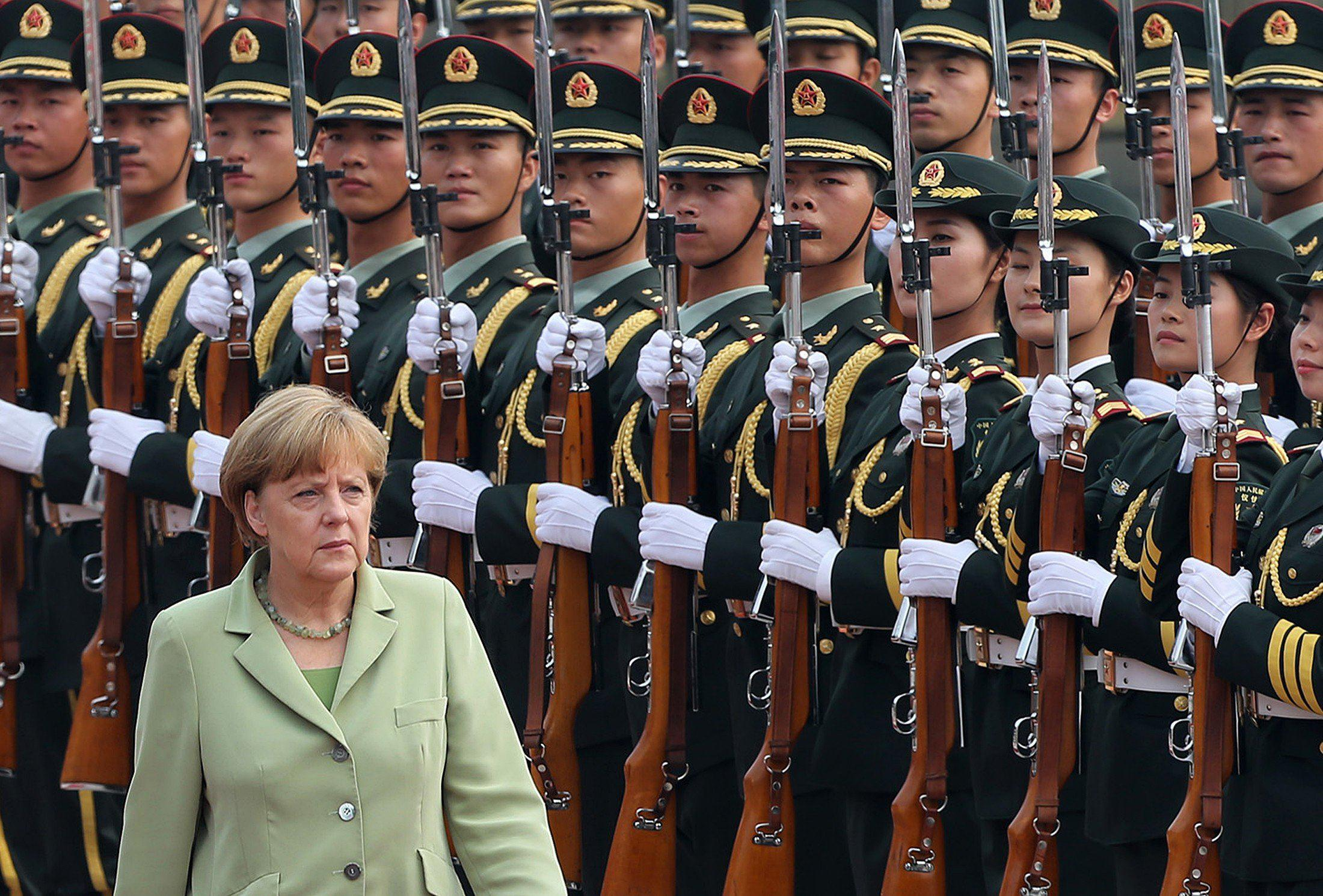 Image: Germany's Chancellor Angela Merkel reviews an honour guard during a welcoming ceremony outside the Great Hall of the People in Beijing