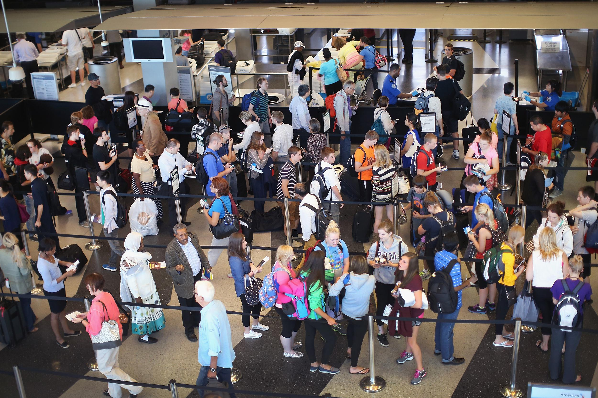 Image: Passengers wait in line at a security checkpoint at O'Hare International Airport on June 17, 2014 in Chicago, Ill.