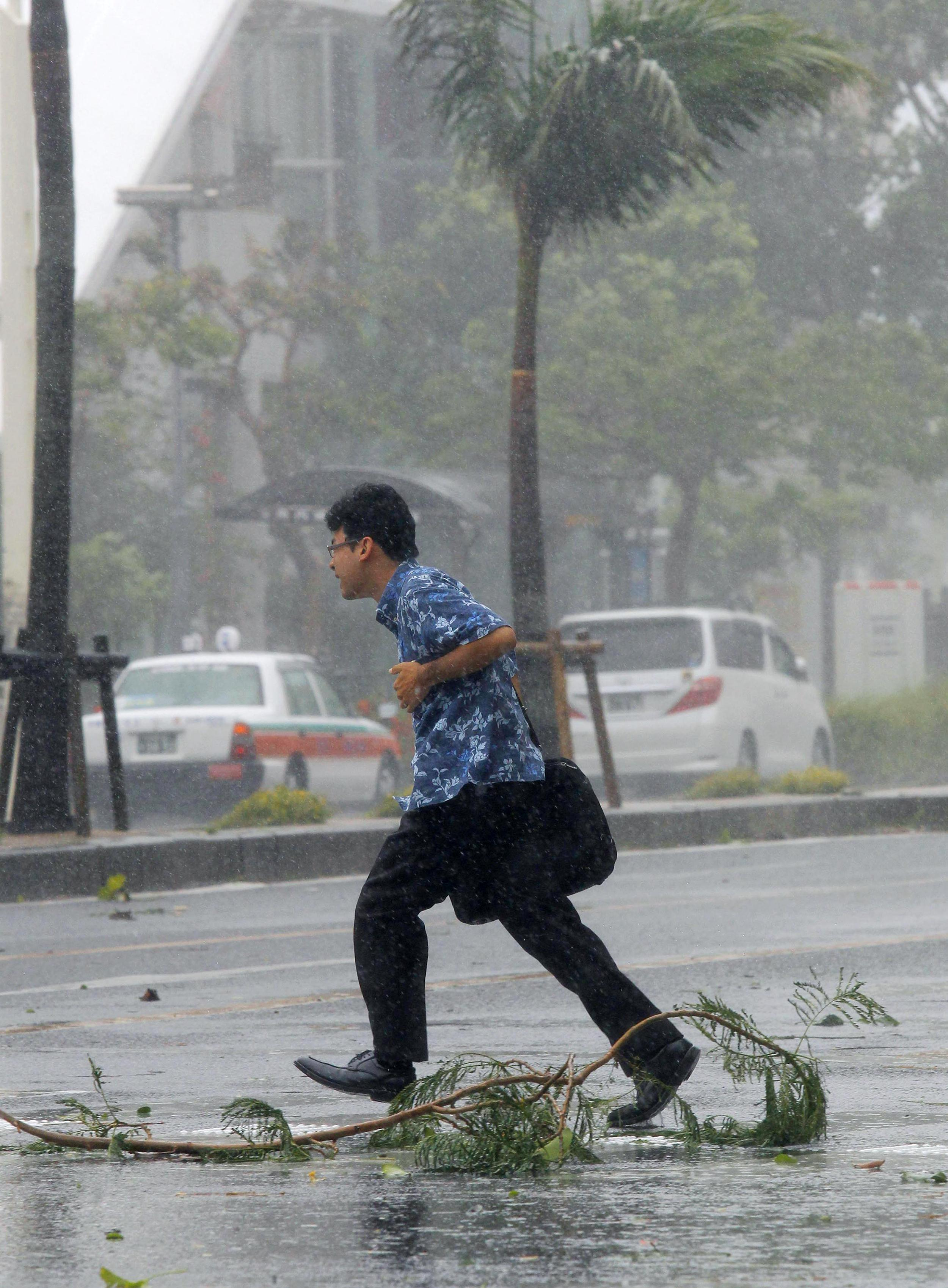 Image: A man walks across a street amid strong winds in Naha, Okinawa, southern Japan,