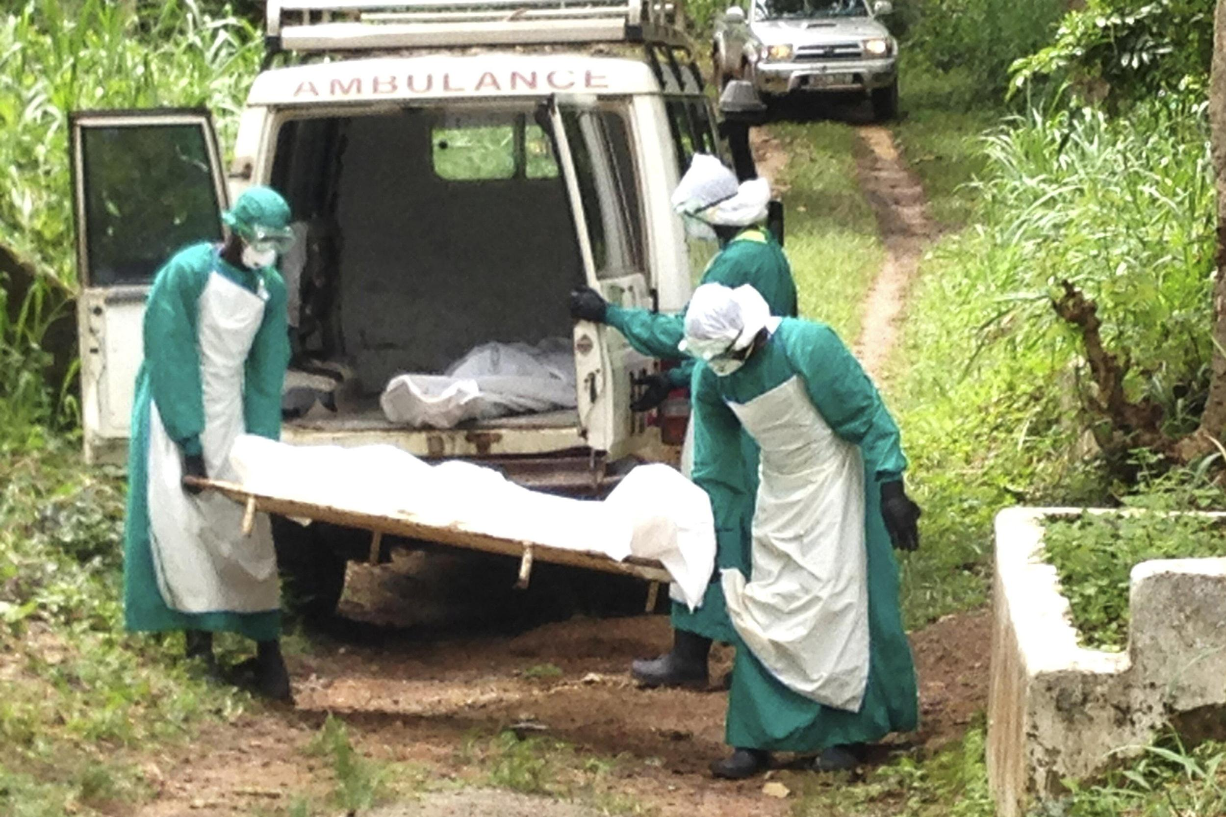 Image: Health workers carry the body of an Ebola virus victim in Kenema