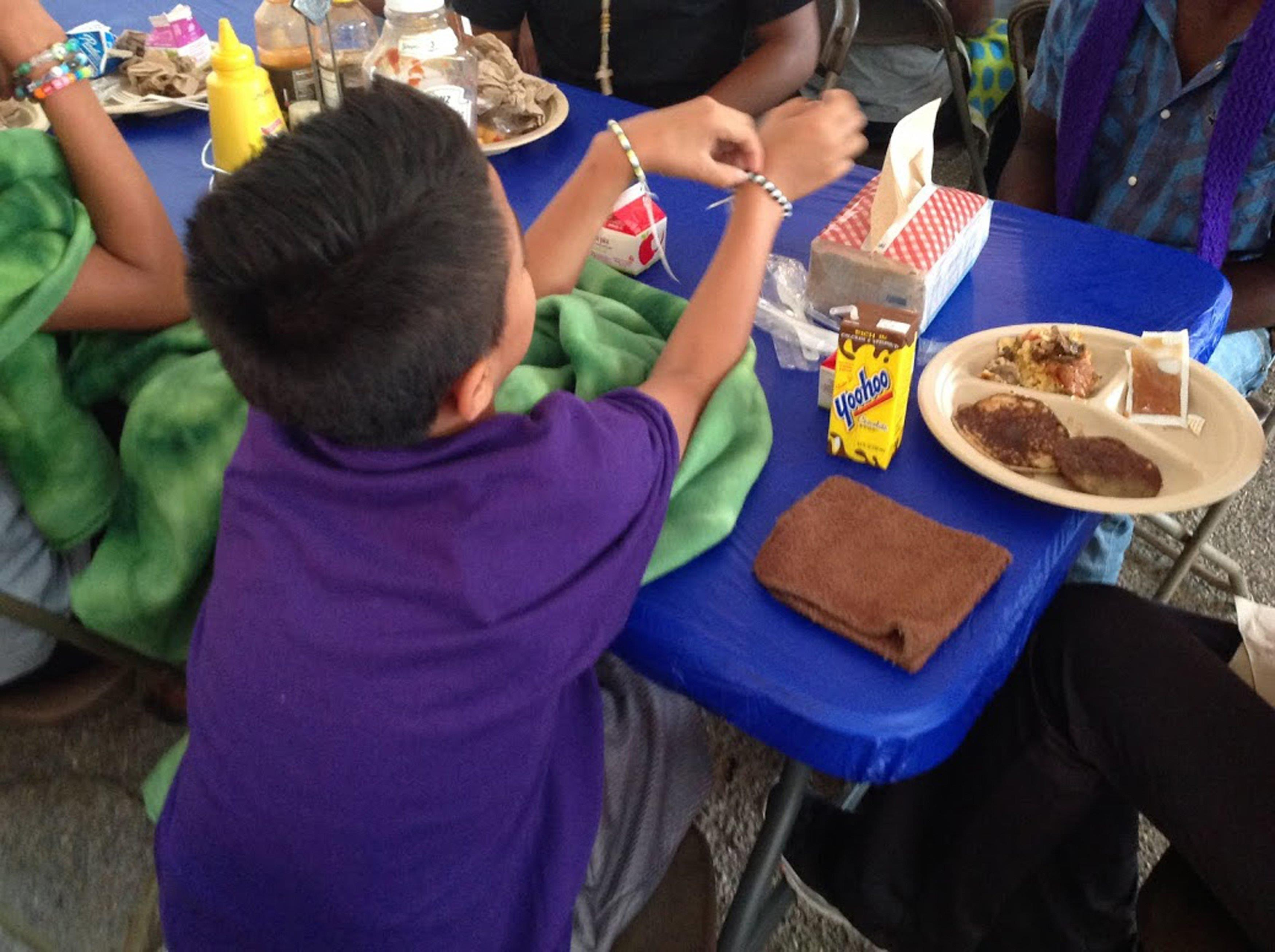 Image: A migrant child sits during a meal at the Naval Base Ventura County Temporary Shelter in Port Hueneme, California