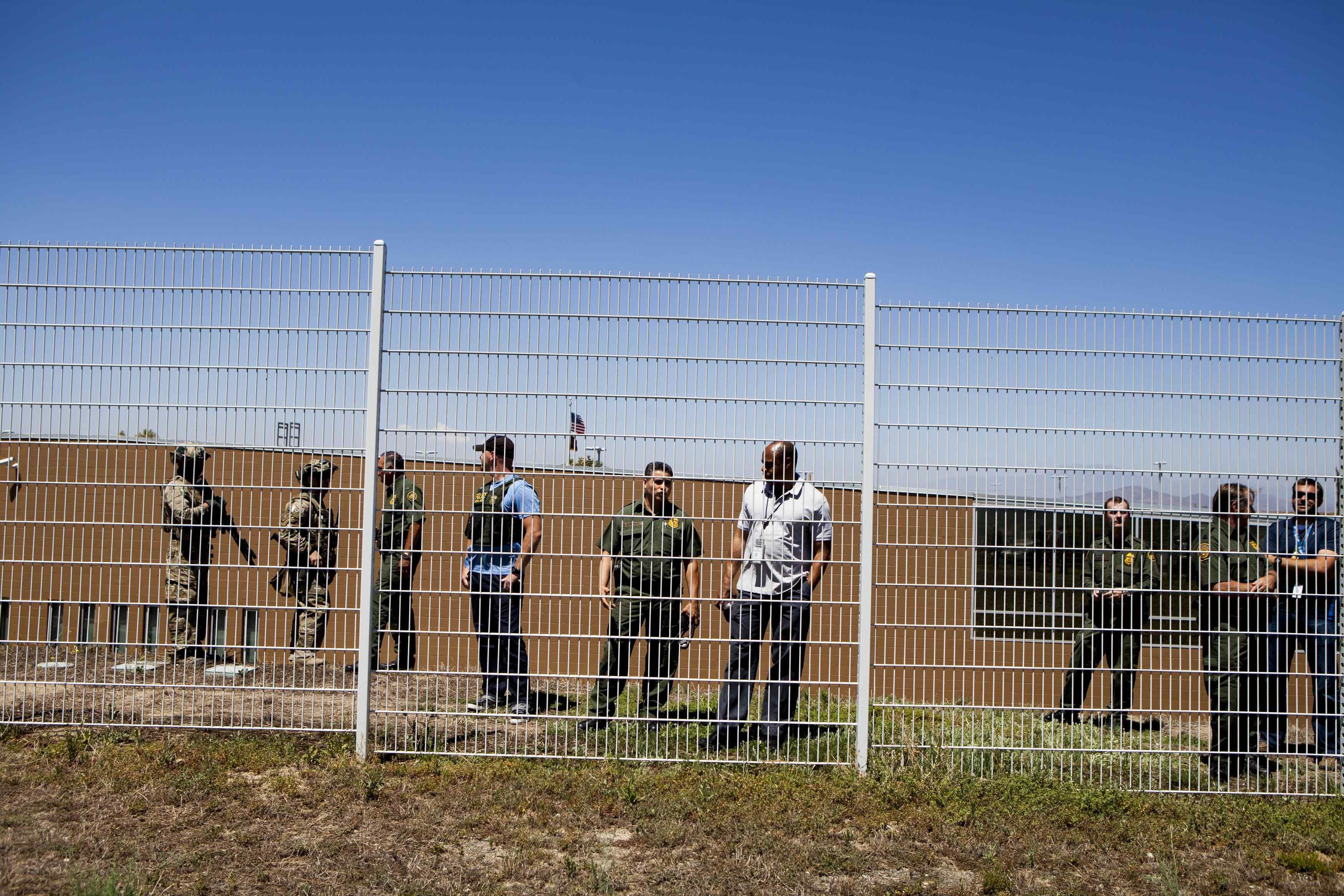 Image: Border Patrol agents watch as demonstrators picket against the possible arrivals of undocumented migrants who may be processed at the Murrieta Border Patrol Station in California